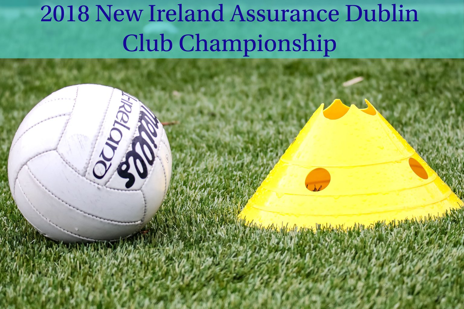White Gaelic Football And Yellow Cone On A Green Grass Pitch With Green Banner With the Wording 2018 New Ireland Assurance Dublin Club Championship
