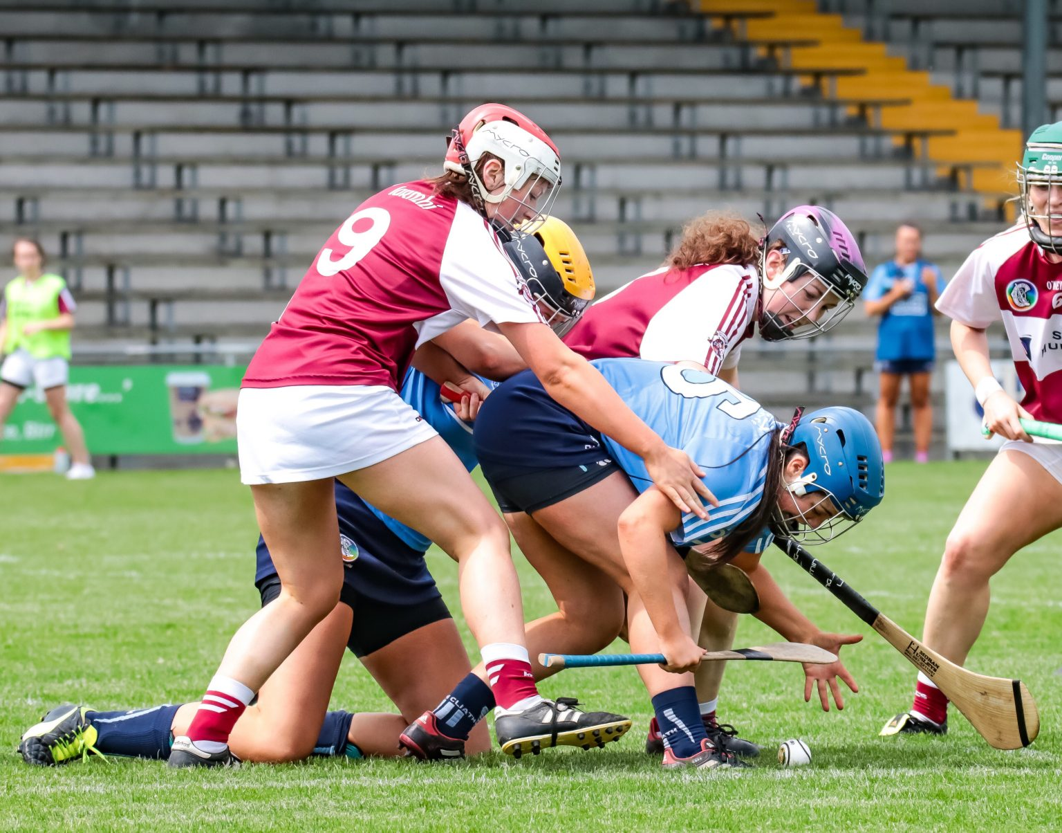 Two Dublin Camogie players in sky blue jerseys battle for the ball with two Westmeath players in maroon jerseys with white sleeves