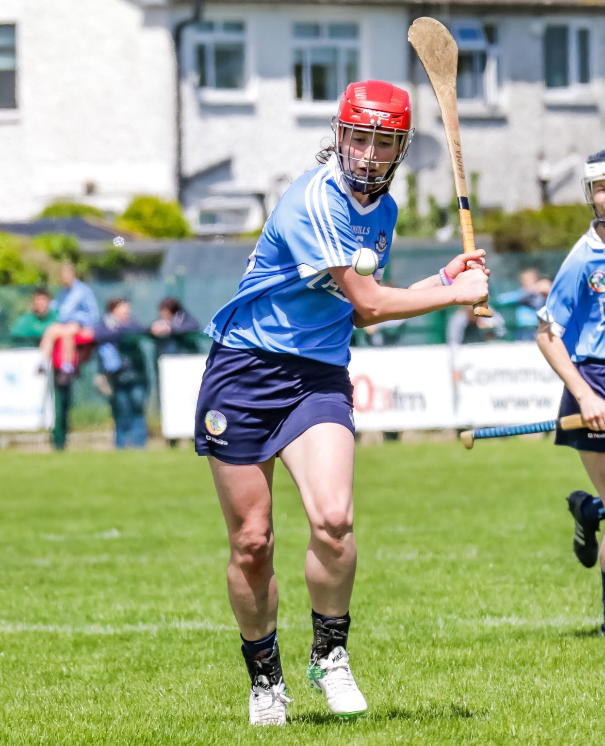 Dublin Player In Sky Blue Jersey and red helmet hitting a white ball with a hurl