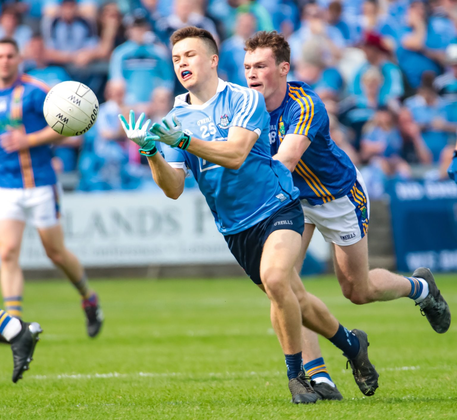A dublin footballer in a sky blue jersey hand passes the white ball in Championship opener