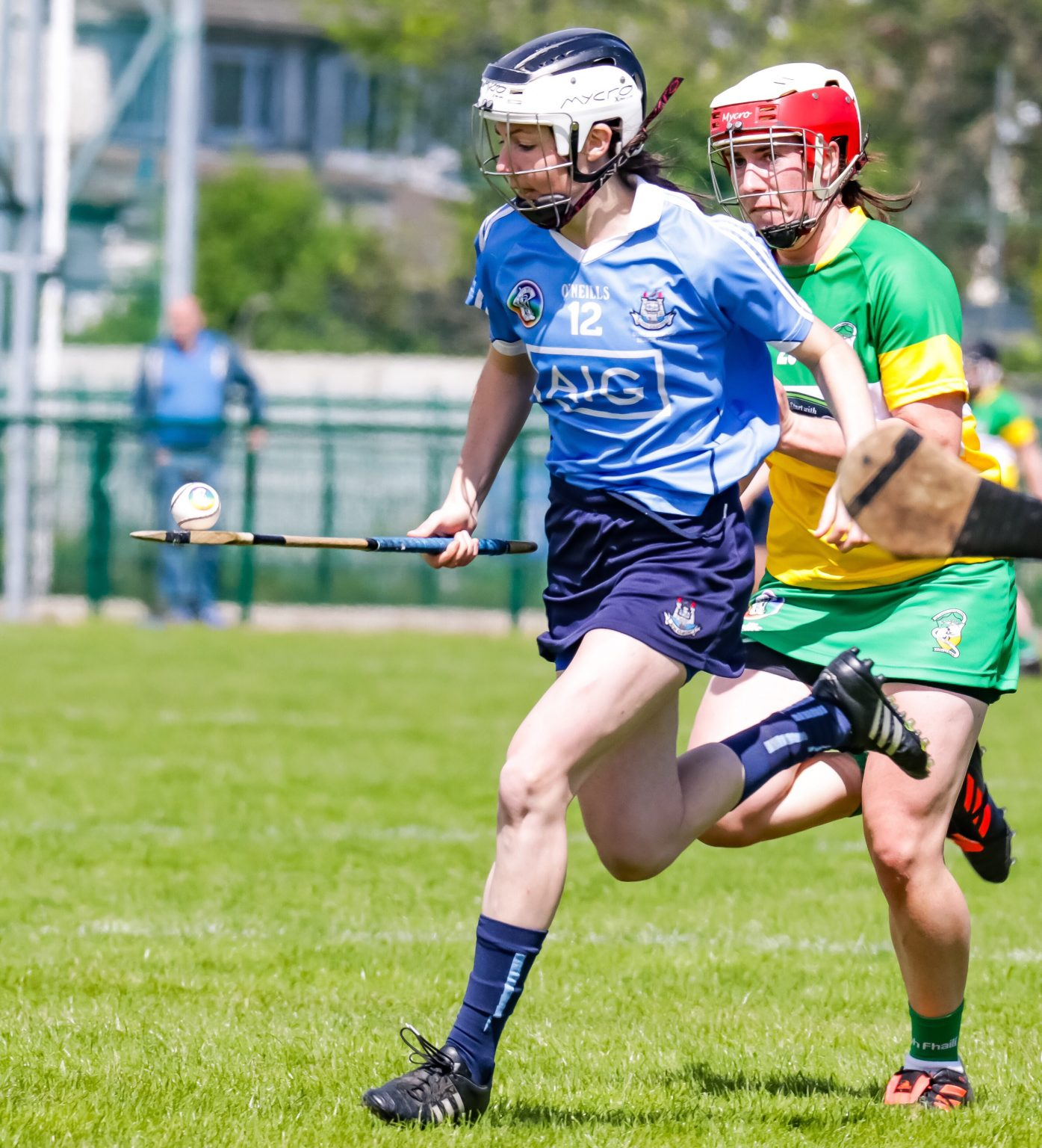 Dublin Camogie Player In A Sky Blue Jersey Running with a white ball balancing on a hurl
