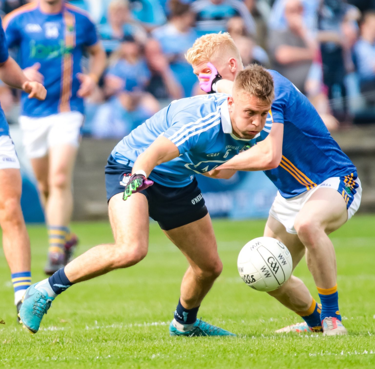 Dublin Footballer Jonny Cooper in a sky blue jersey battled for the ball against a Wicklow Player in a dark blue jersey with yellow stripes in Championship opener