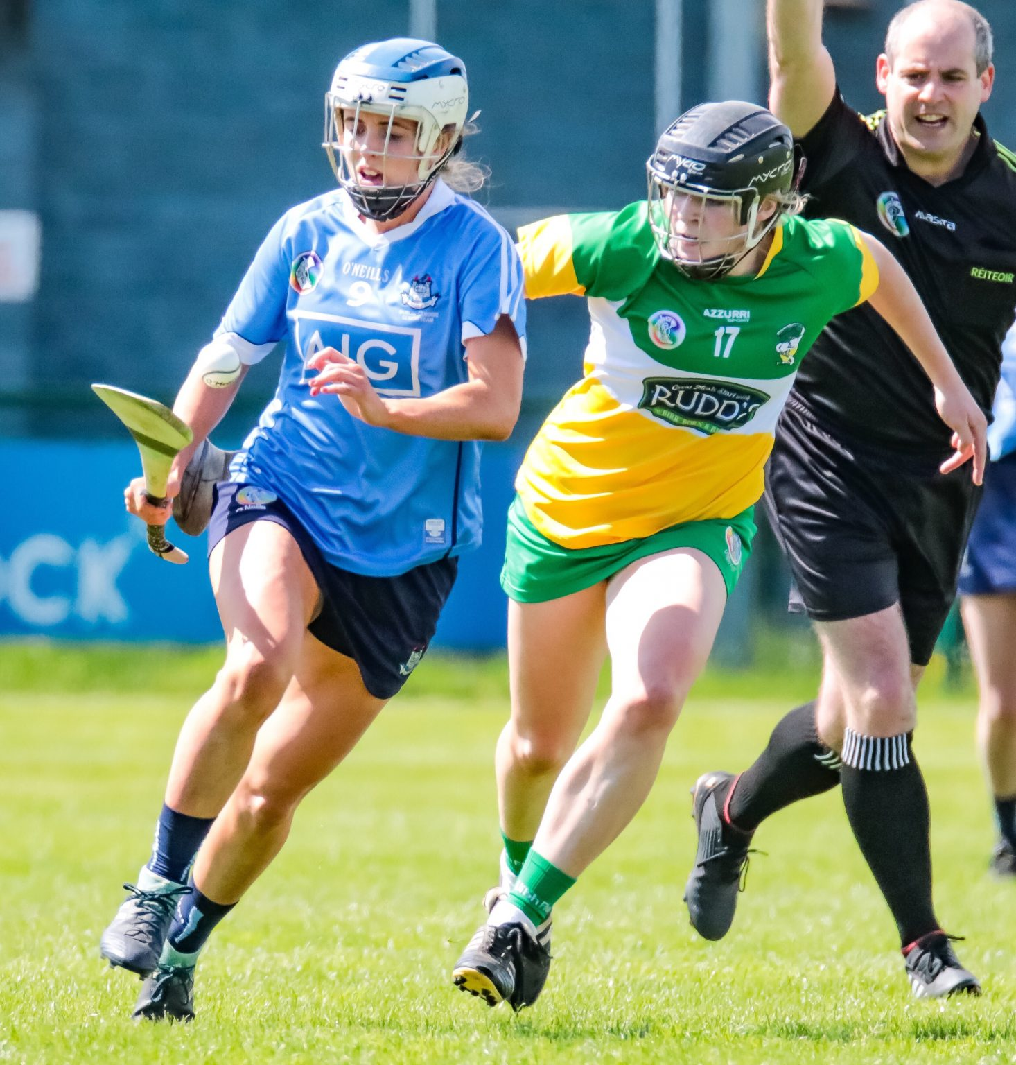 Dublin Player In a Sky Blue Jersey running away from an Offaly Player In a green, white and yellow jersey bouncing a white ball on a hurl