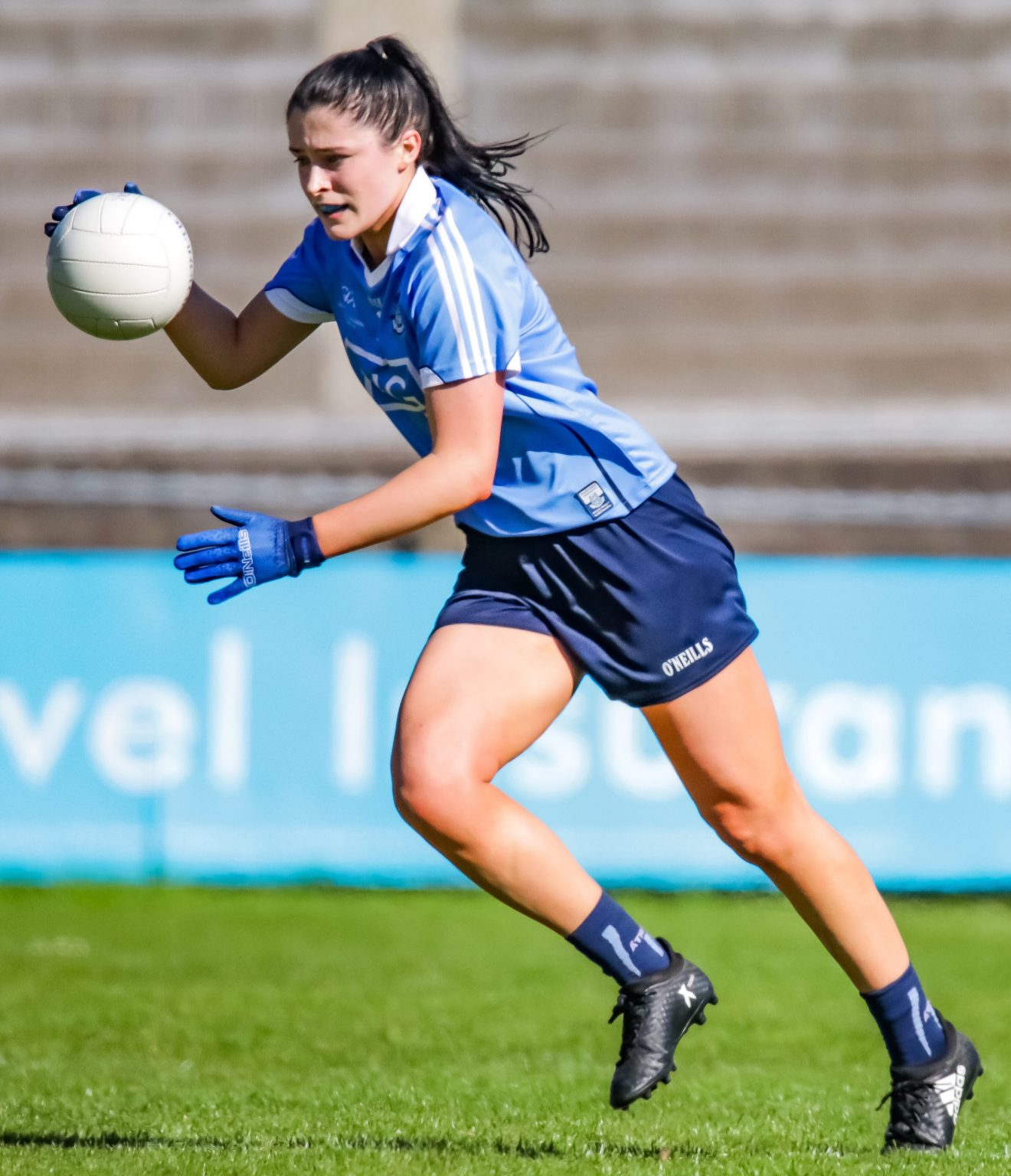 Dublin LGFA Player Olwen Carey in a sky blue jersey running with a white ball