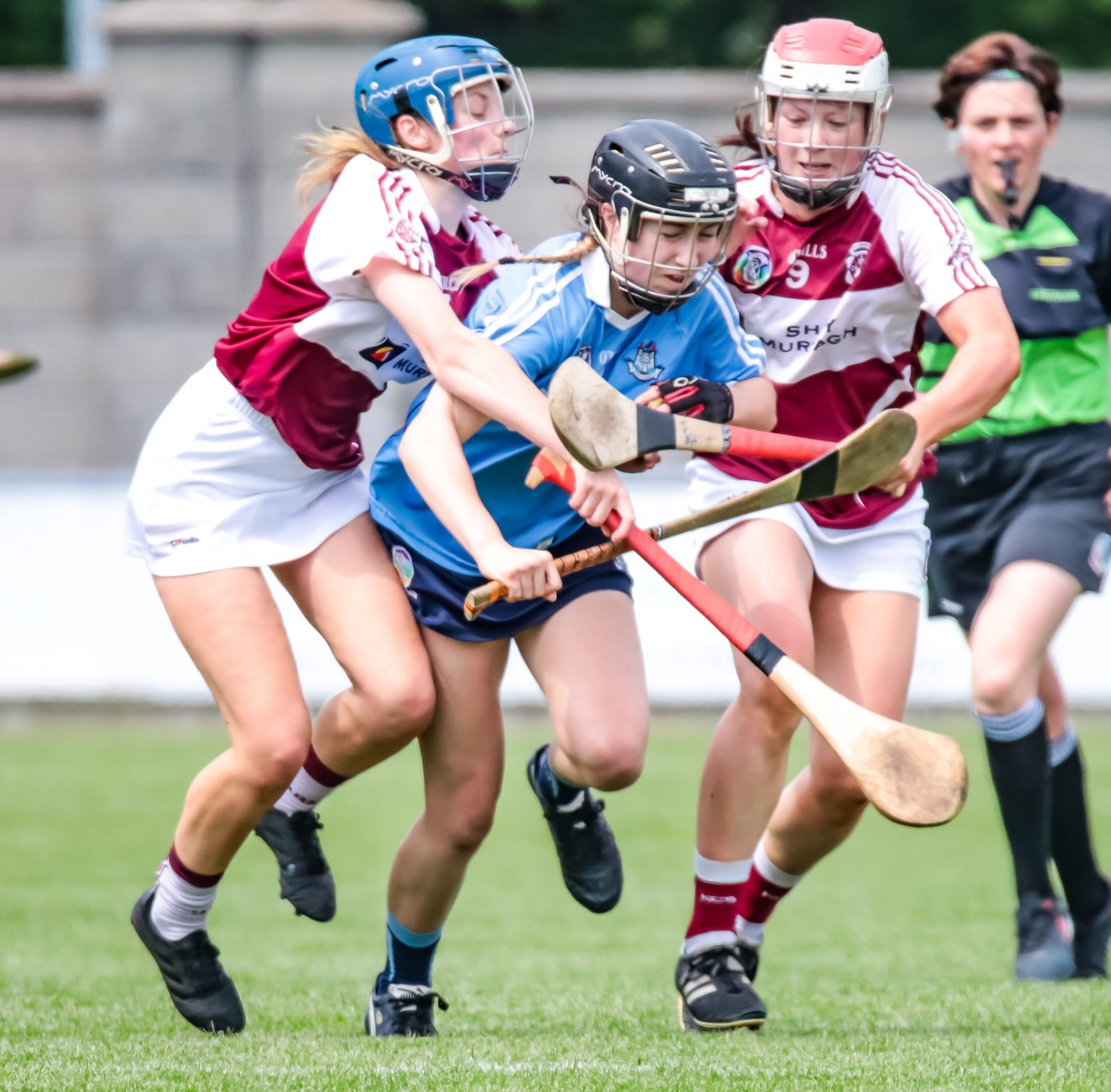 Dublin Camogie Player In Sky Blue Jersey tried to break free from two Westmeath players in maroon jersey with white sleeves in the championship final which seen Westmeath win the Leinster title