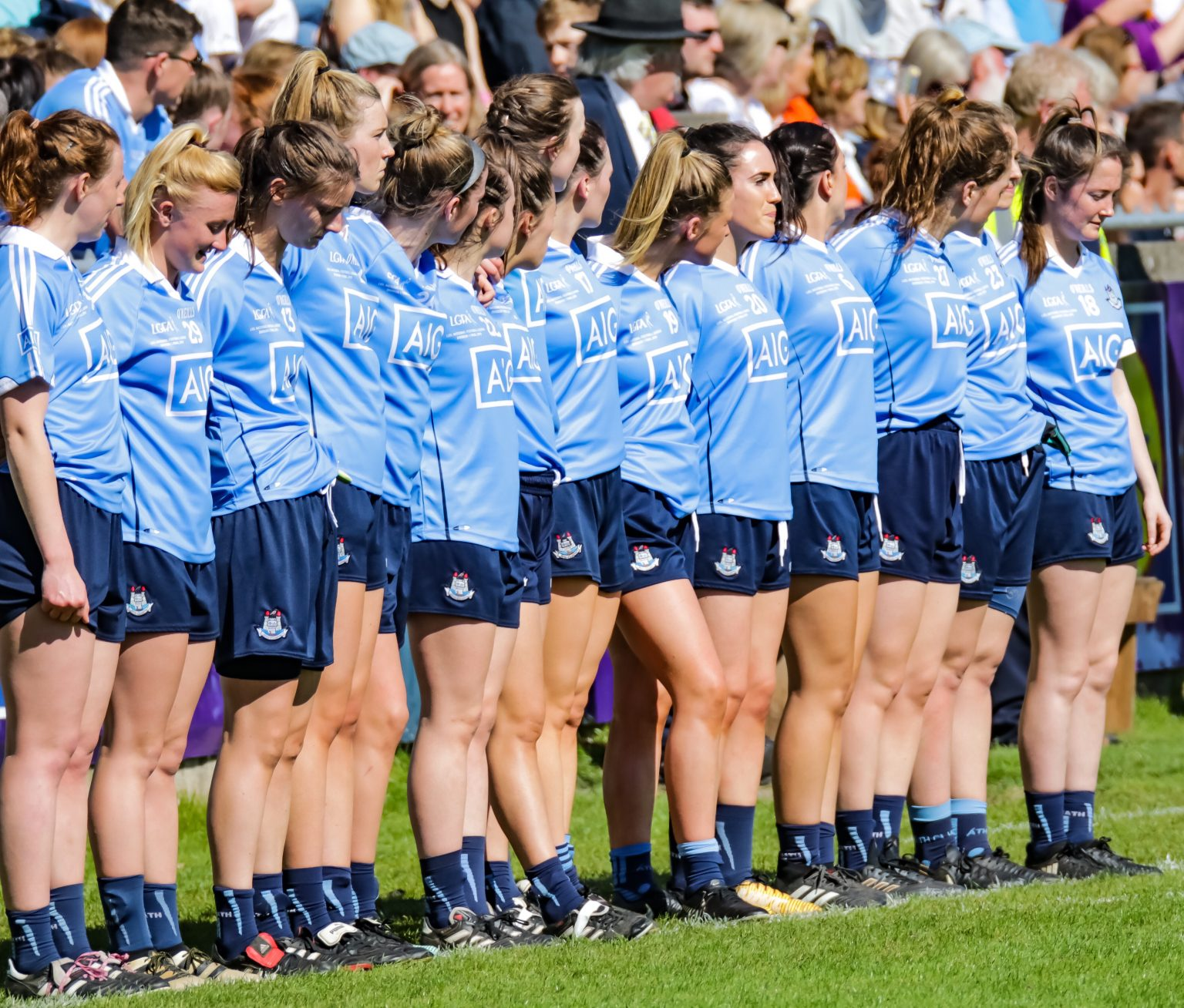 Twelve Dublin Ladies Football players in sky blue jerseys stand shoulder to shoulder along the sideline