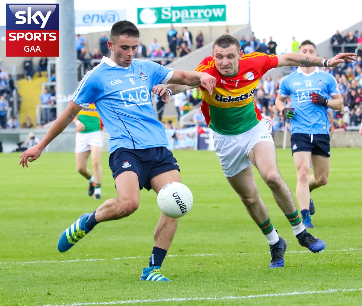 Dublin Player In Sky Blue Jersey About To Kick White Ball As He Is Tackled By A Carlow Player In a Red, Yellow And Green Jersey On A Green Pitch With A Sky Sports Logo