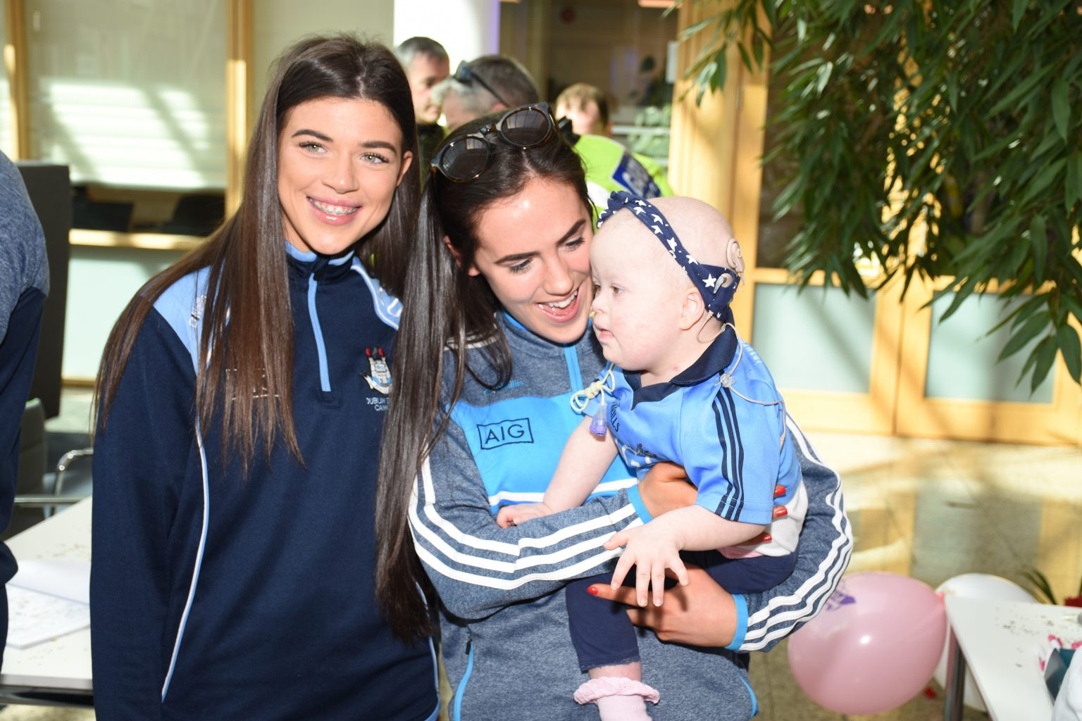Dublin Players Hannah O'Neill and Emma O'Byrne holding a baby at the Aoibheann's Pink Tie Announcement In AIG Headquarters
