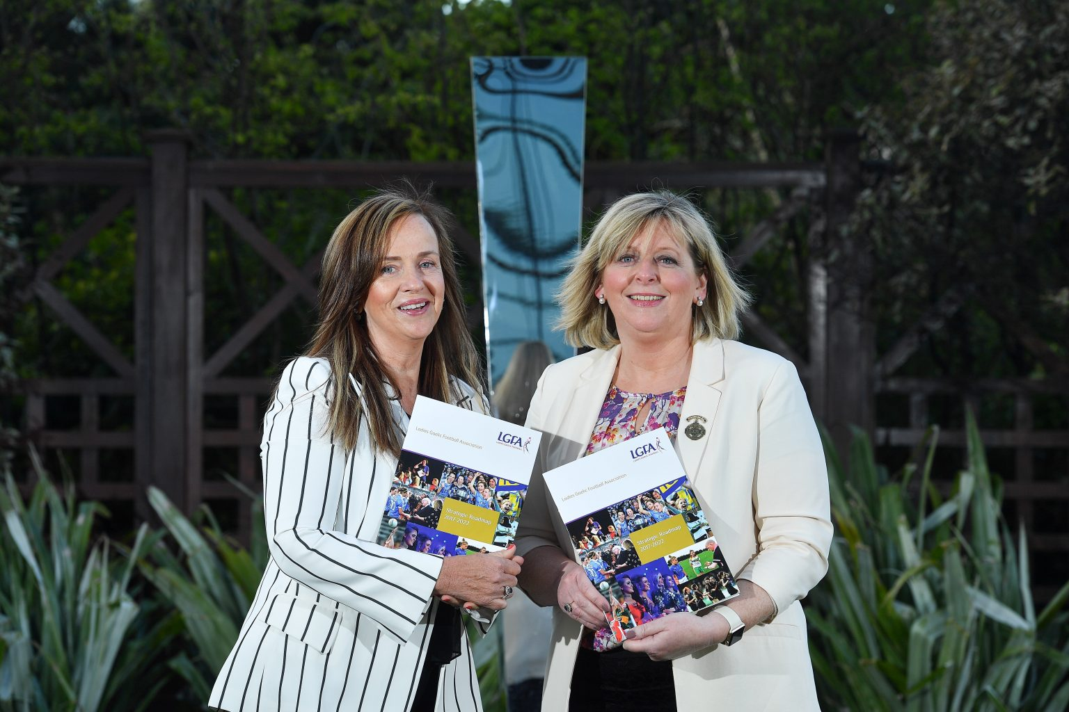 Two Ladies one in a white jacket with black stripes and other in plain white jacket holding the Ladies Gaelic Football Association stratgegic roadmap booklet