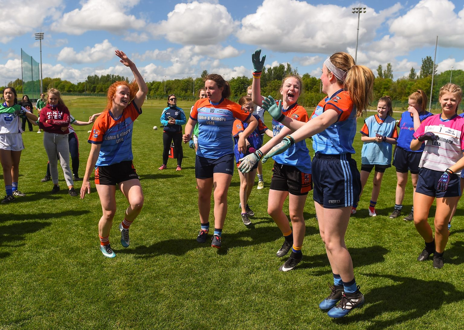 Four players in a blue jersey with red sleeves dancing on the pitch at the Gaelic4Teens programme