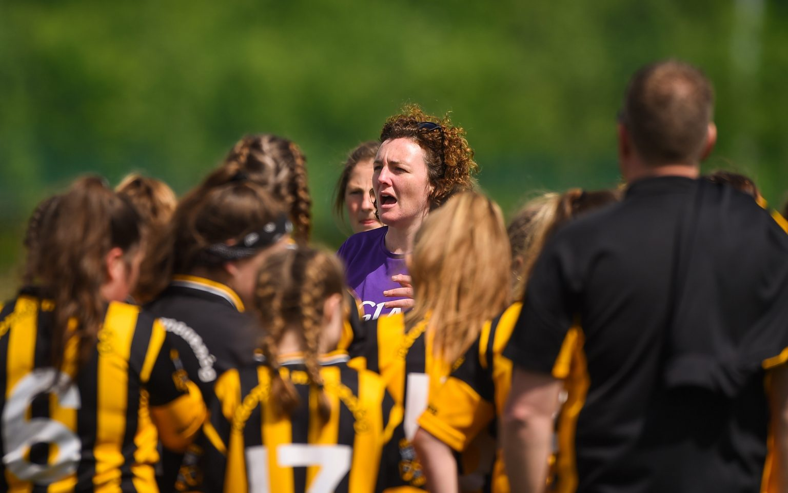 Coach in purple jersey giving instructions to a group of players wearing amber with horizontal black stripes at the Gaelic4Teens programme