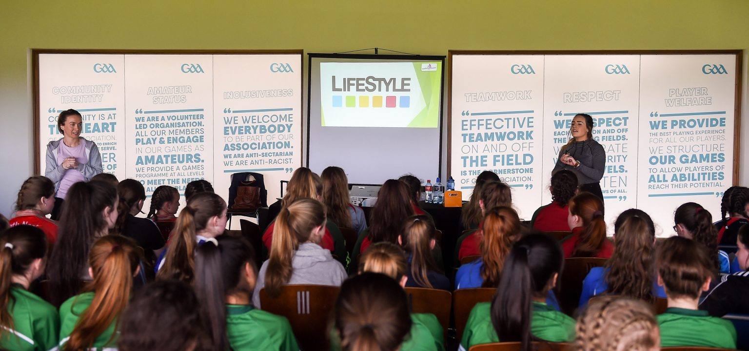 Large group of players sit listening to a lecture at the Gaelic4Teens programme