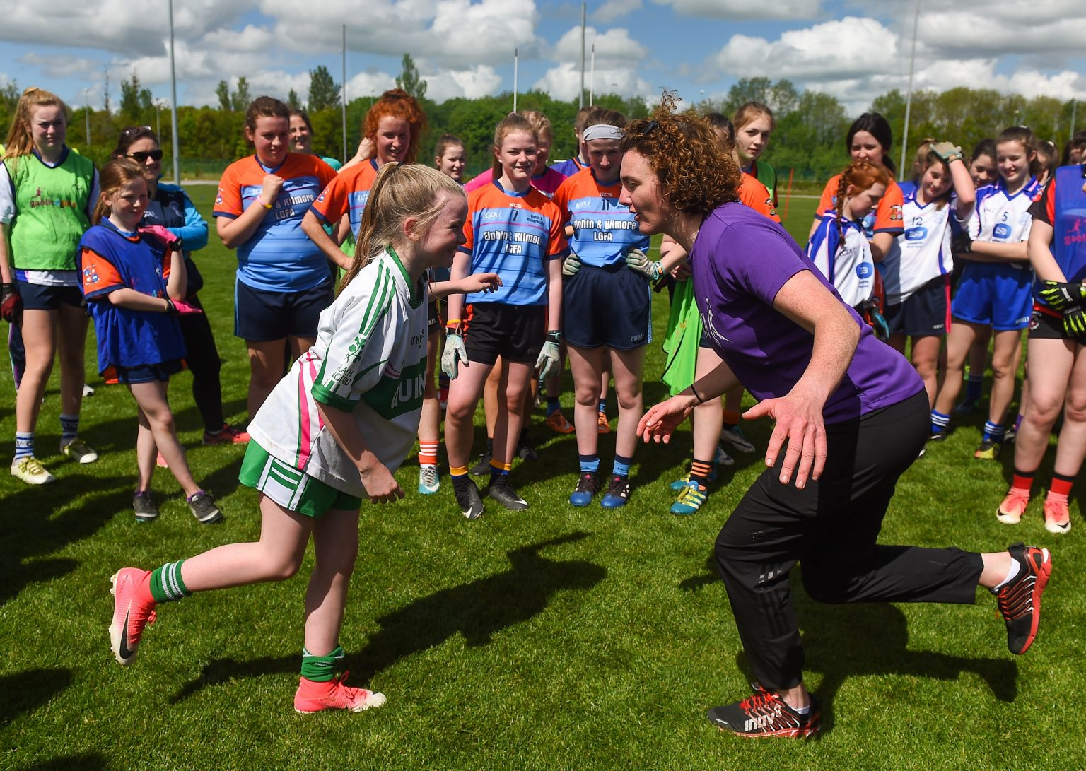 Young Player in white jersey with red and green stripes and a coach in a purple jersey face each other standing on one leg at the Gaelic4Teens programme