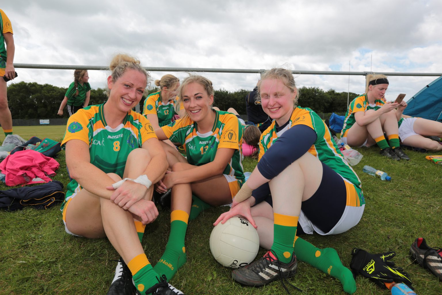 Three ladies football players in green jersey with yellow sleeves sitting on the grass at the Interfirms competition