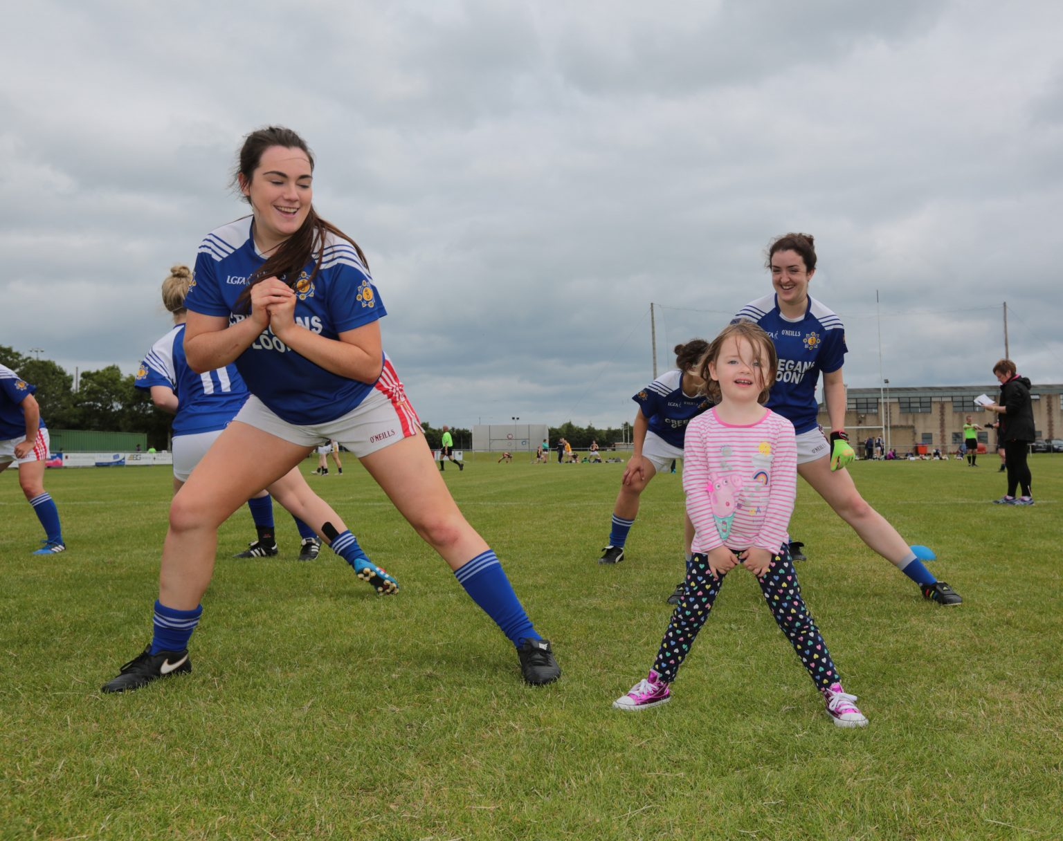 Two ladies football players in a dark blue jersey doing stretching exercise with a young girl in a pink top and black polka dot trousers