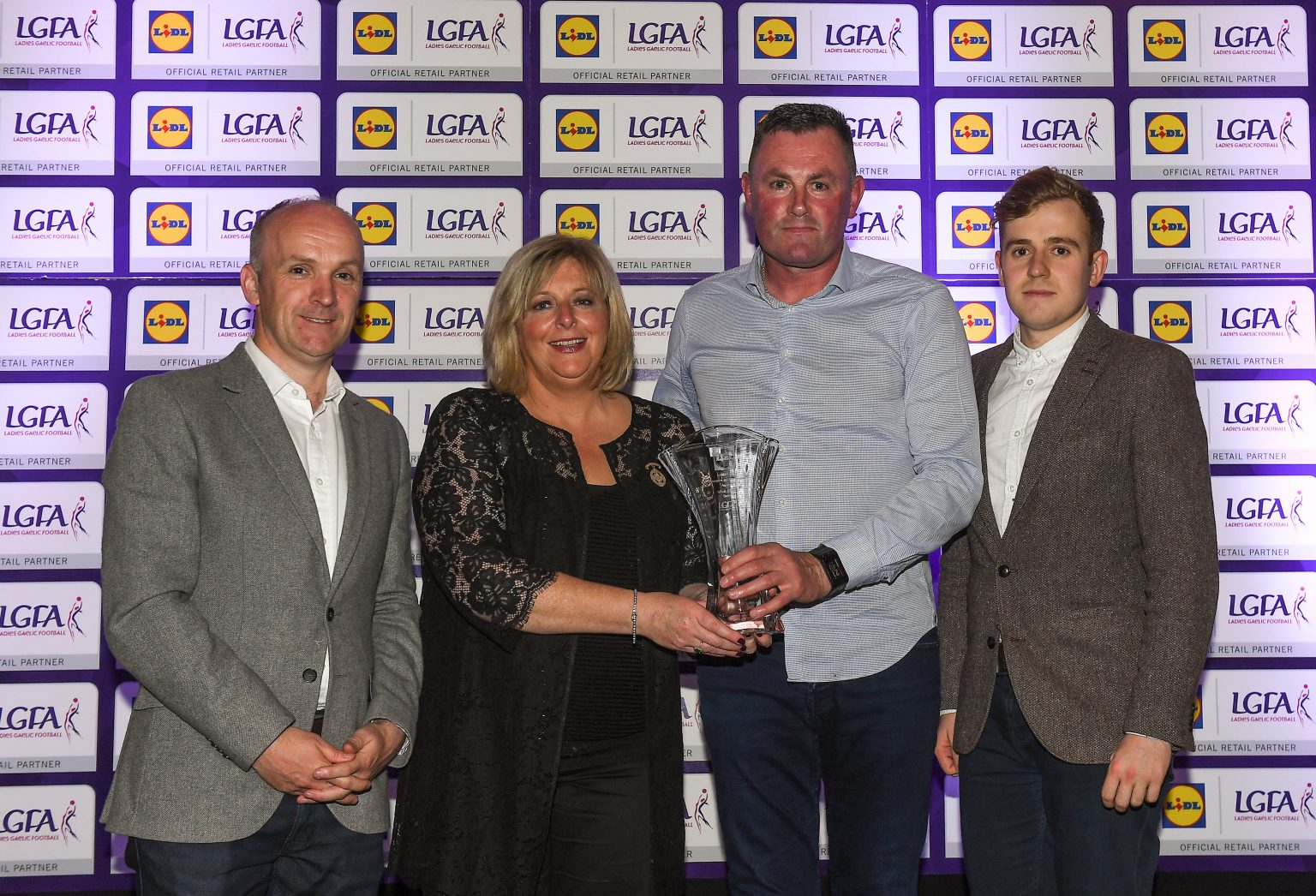 Dublin manager Mick Bohan in a grey shirt is presented with his manager of the league award by LGFA president Marie Hickey in a black lace dress with two men either side in grey suit jackets and white shirts