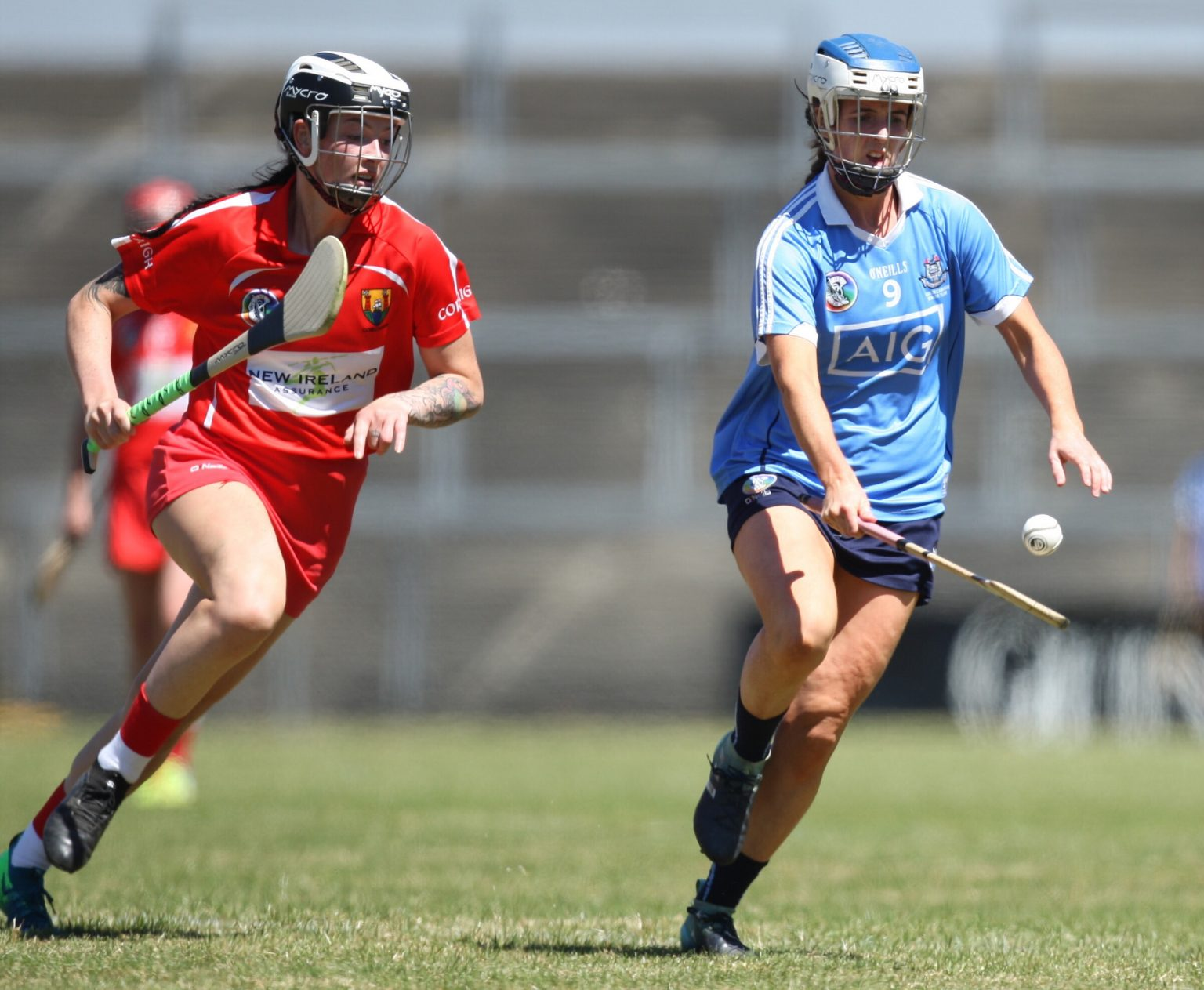 Dublin Camogie player in a sky blue jersey and navy skort bounces the ball on her hurl as she breaks away from a Cork player in red jersey
