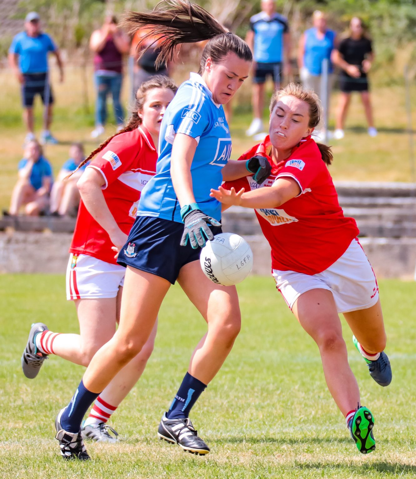 Dublin Player in a sky blue jersey is tackled by a Cork Minor Ladies Footballer in a red jersey