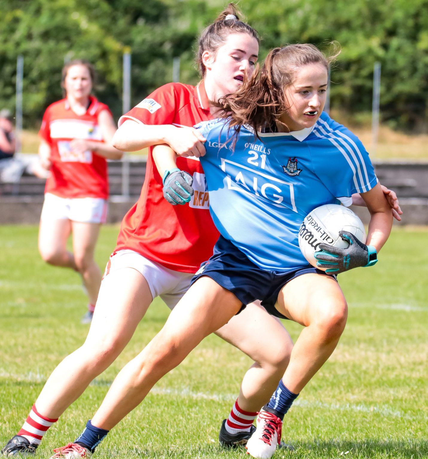 A Dublin Minor Ladies footballer tries to break the tackle from a Cork player in a red Jersey