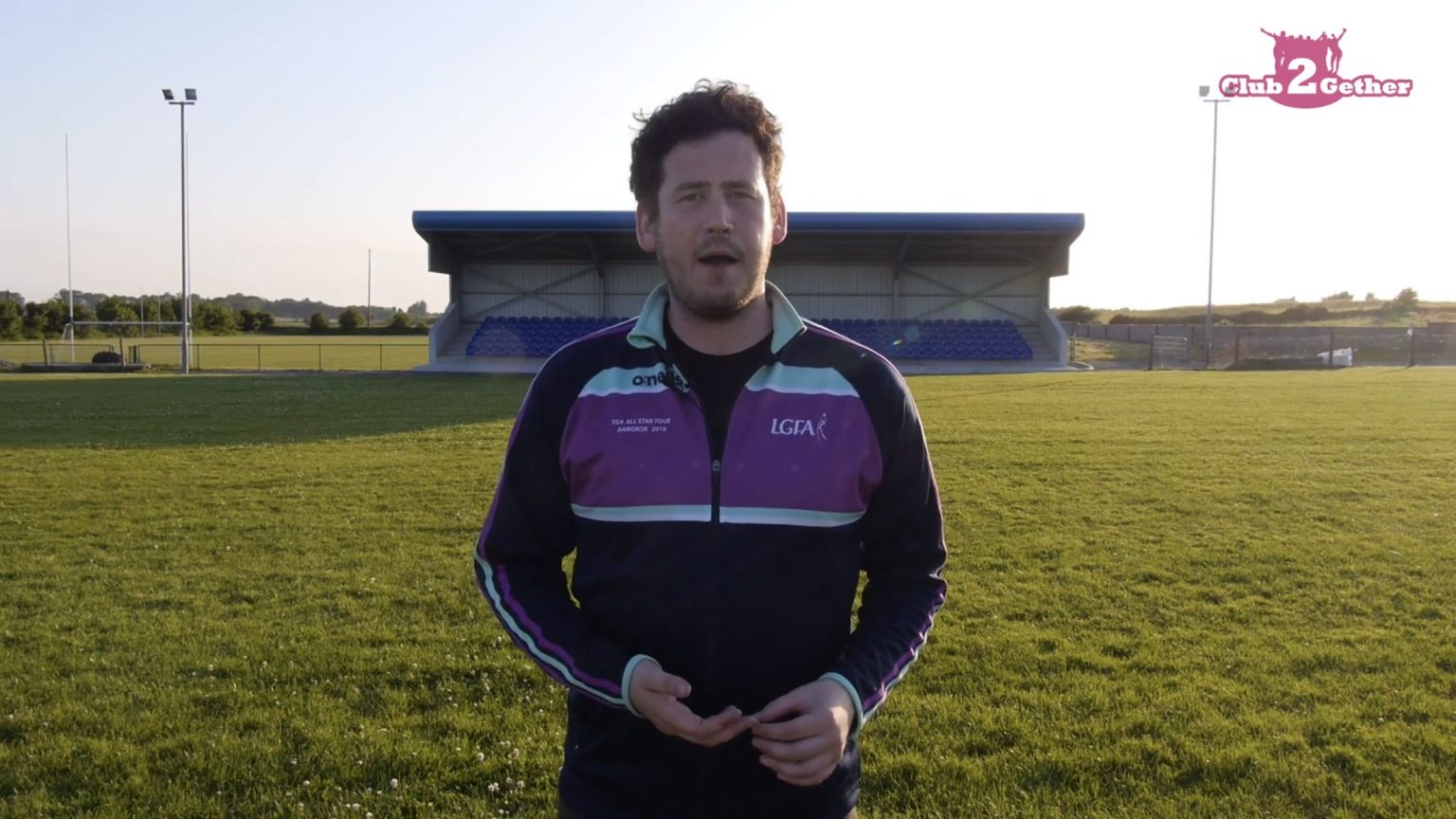 LGFA Office In navy half zip top with purple panel on chest on a pitch with small stand behind him explains the LGFA Club2Gether Programme