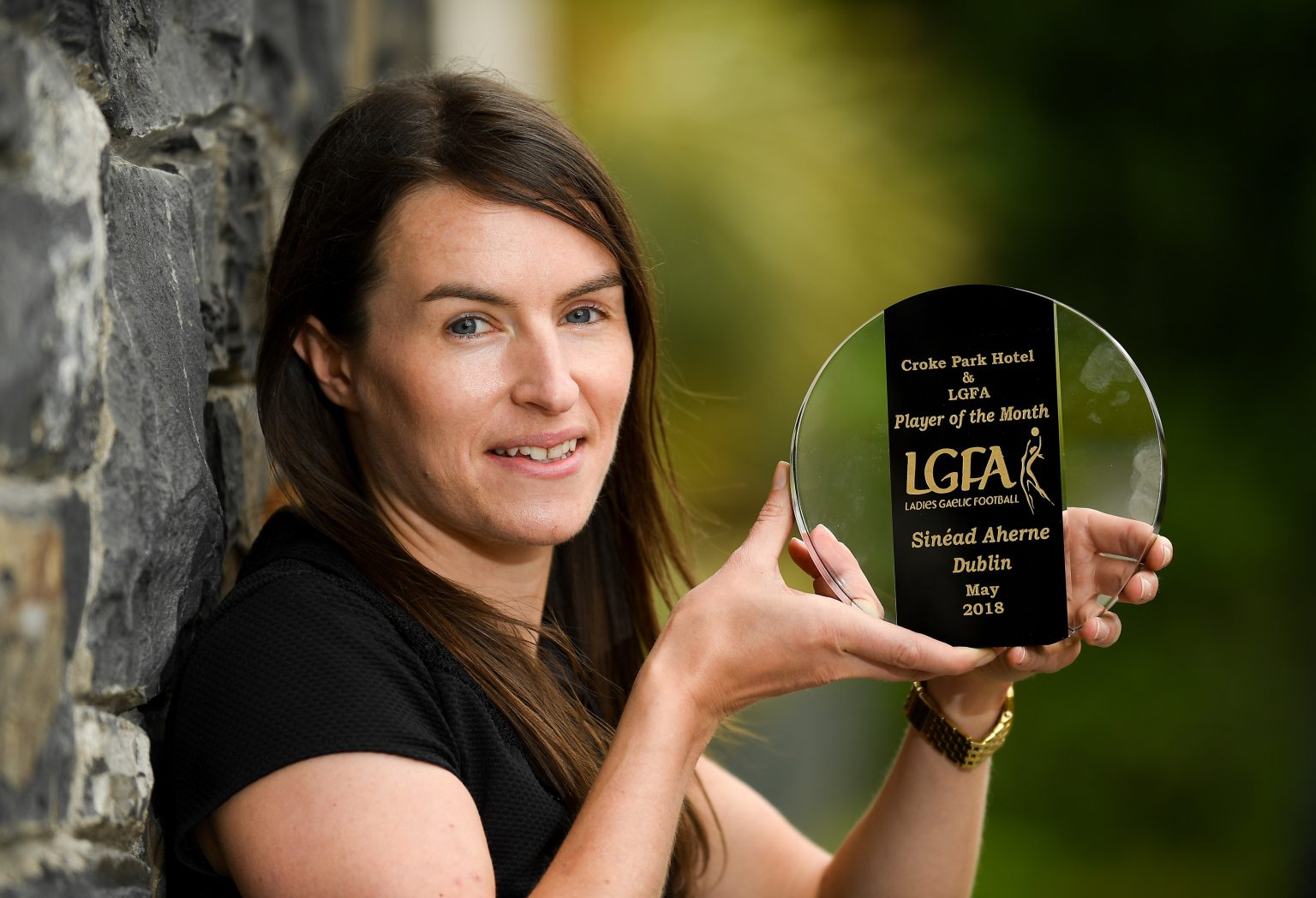 Dublin Captain Sinead Aherne in a black dress leaning against a tree trunk holding her Croke Park Hotel/ LGFA Player Of The Month award for May