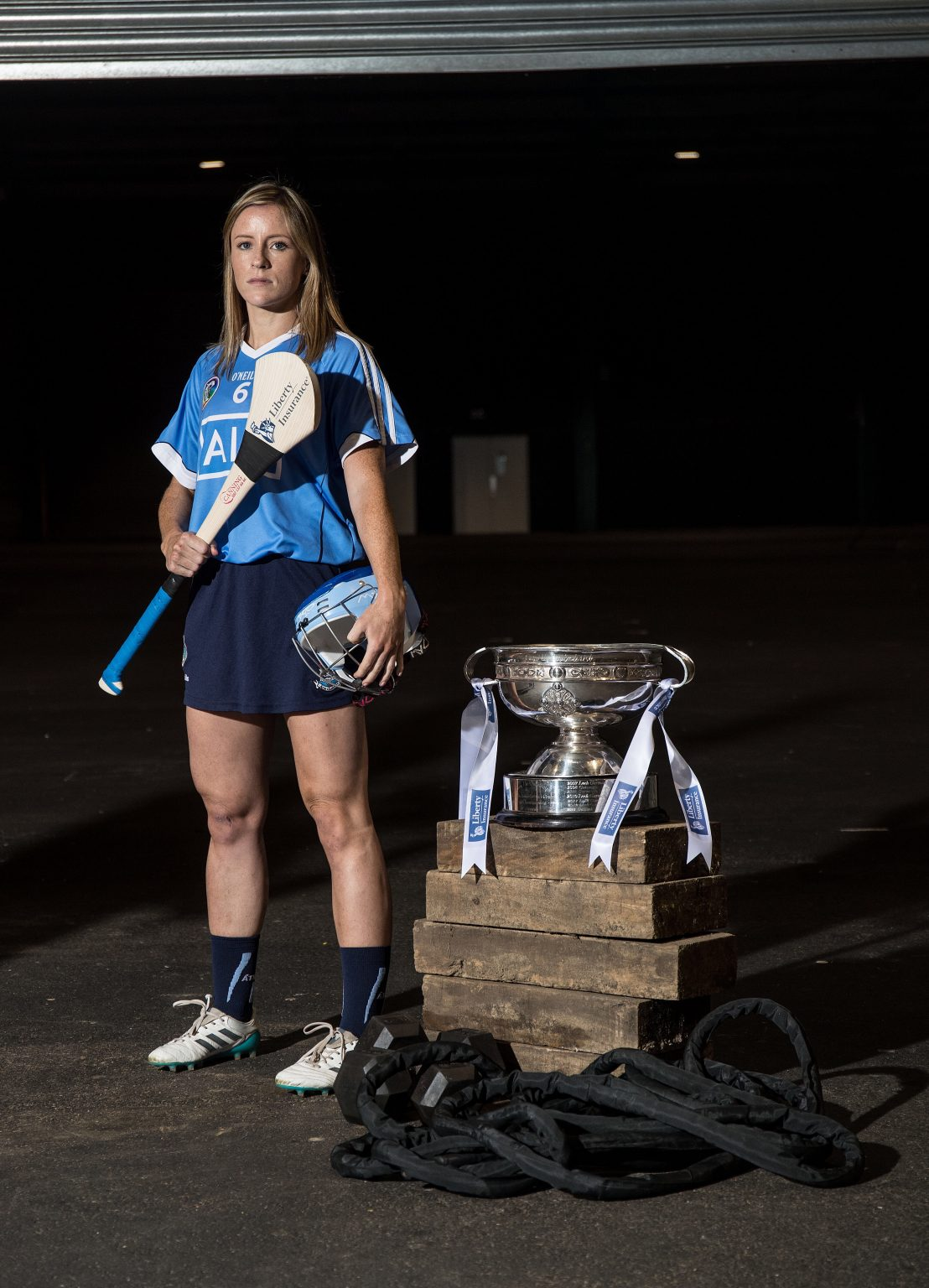 Dublin Camogie player Laura Twomey in a sky blue jersey, holding a hurl in her right hand and helmet in her left hand pictured with the O'Duffy Cup at the launch of the All Ireland Camogie Championhips.