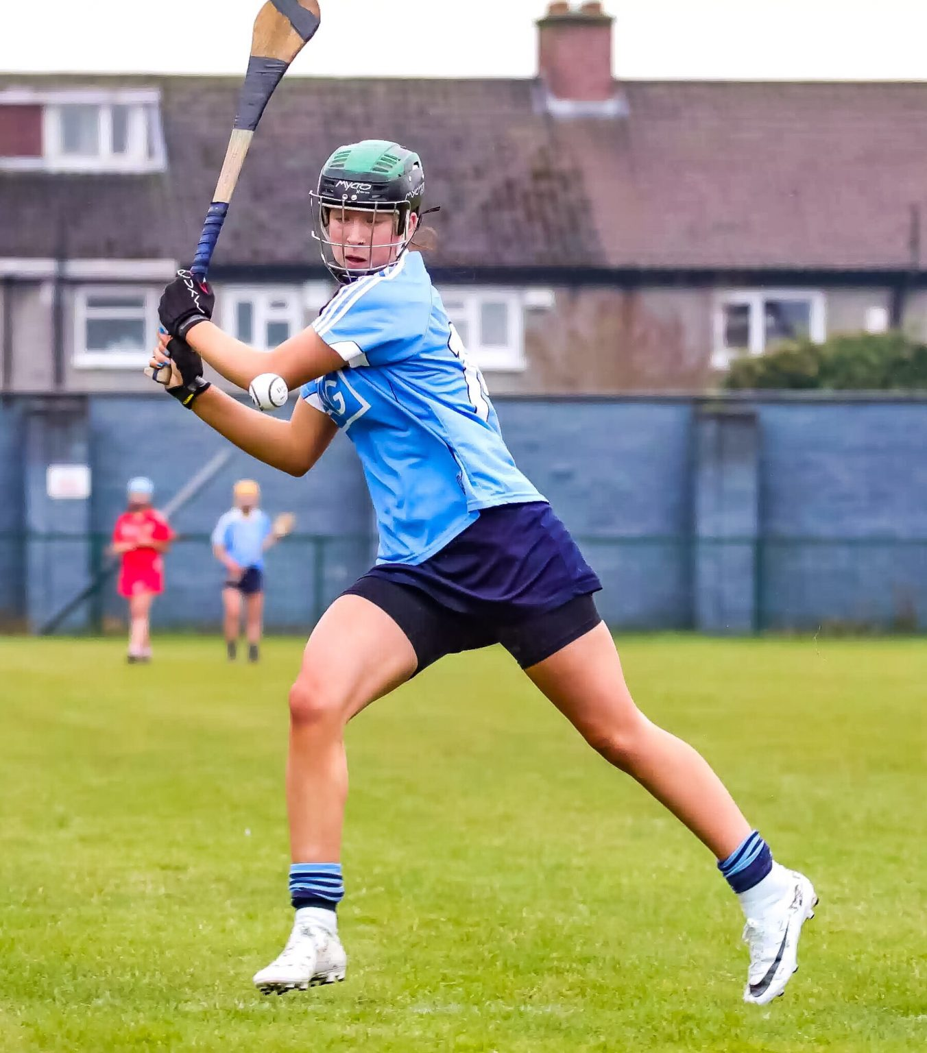 Dublin Camogie player in a sky blue jersey, navy skort, black and green helmet striking a ball with her hurl during Leinster Minor A game