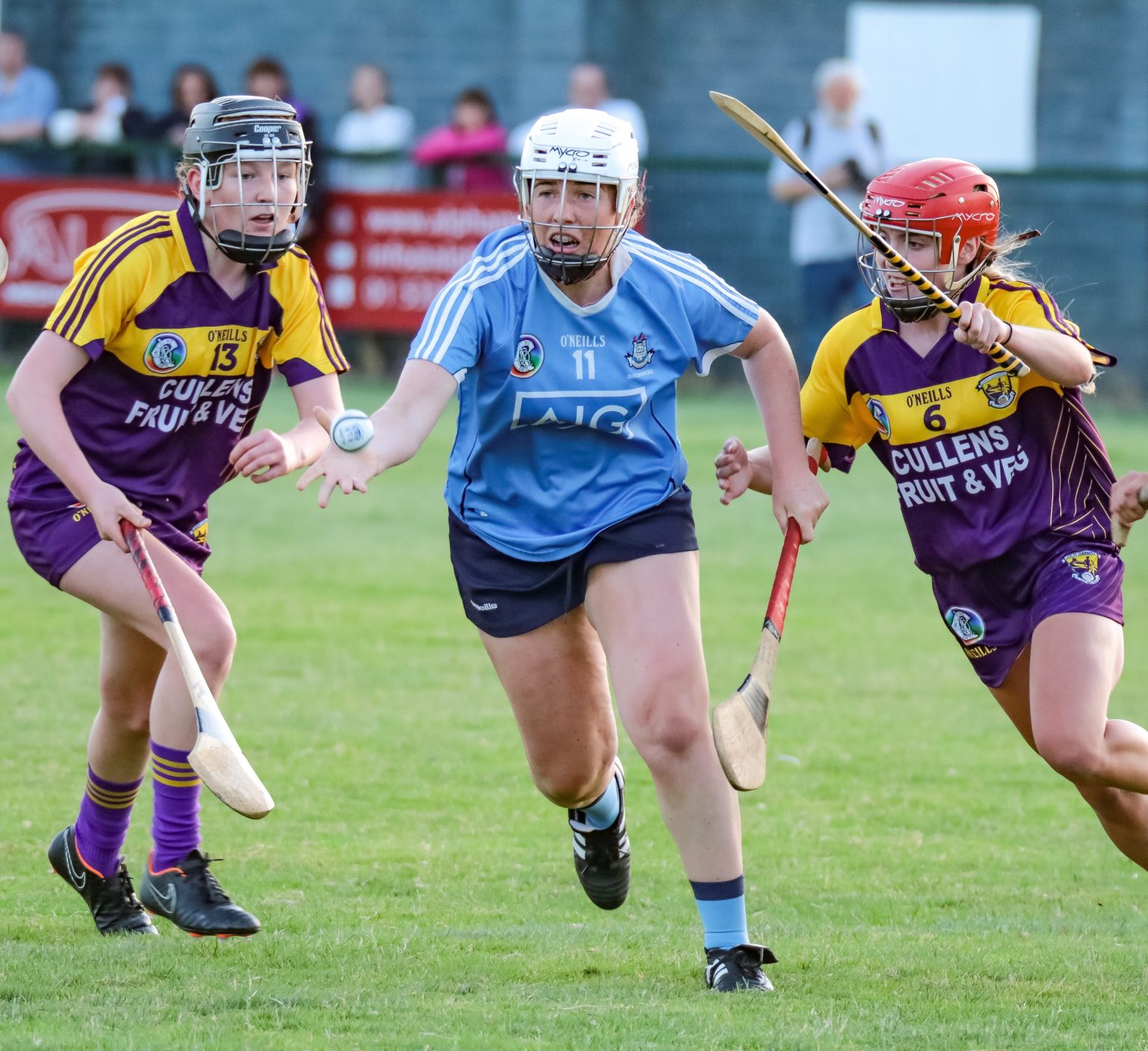 A Dublin Camogie player in a sky blue jersey, navy skort and white helmet hand passes the ball between two Wexford players in purple and gold jerseys, purple skorts and red and black helmets in the Leinster Minor camogie semi final