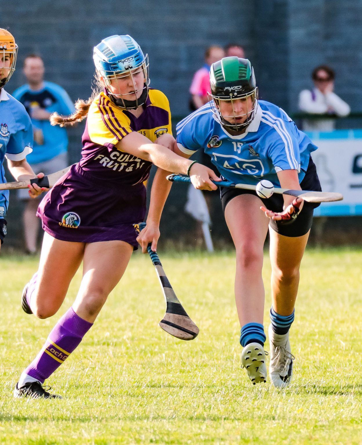 A Dublin Camogie player in a sky blue jersey, navy skort and black and green helmet and a Wexford players in a purple and gold jersey and purple skort battle for the ball in the Leinster Minor Camogie semi final