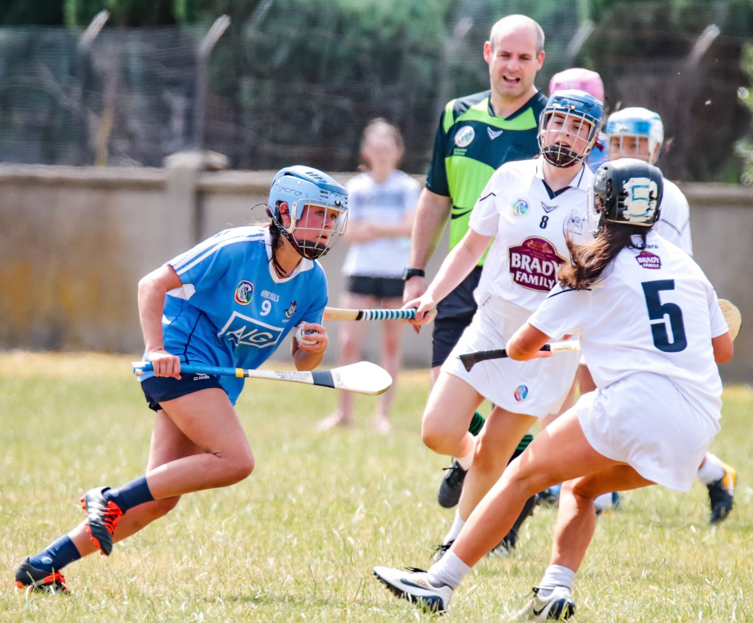 Dublin Minor Camogie Player in a sky blue jersey and sky blue and blue helmet in action against three Kildare players in white jerseys