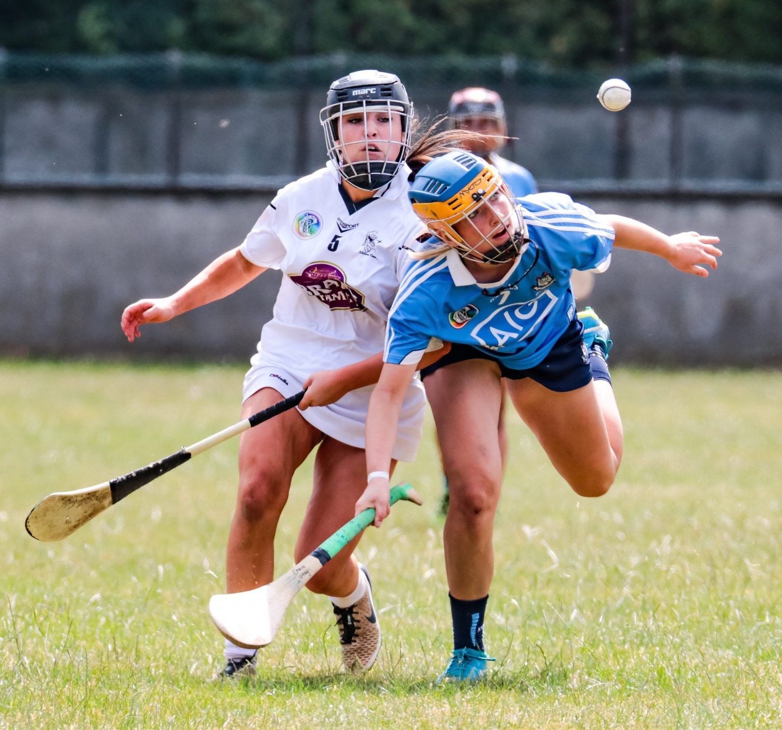 A Kildare Minor Camogie player in a white jersey and a Dublin player in a sky blue jersey battle for the ball