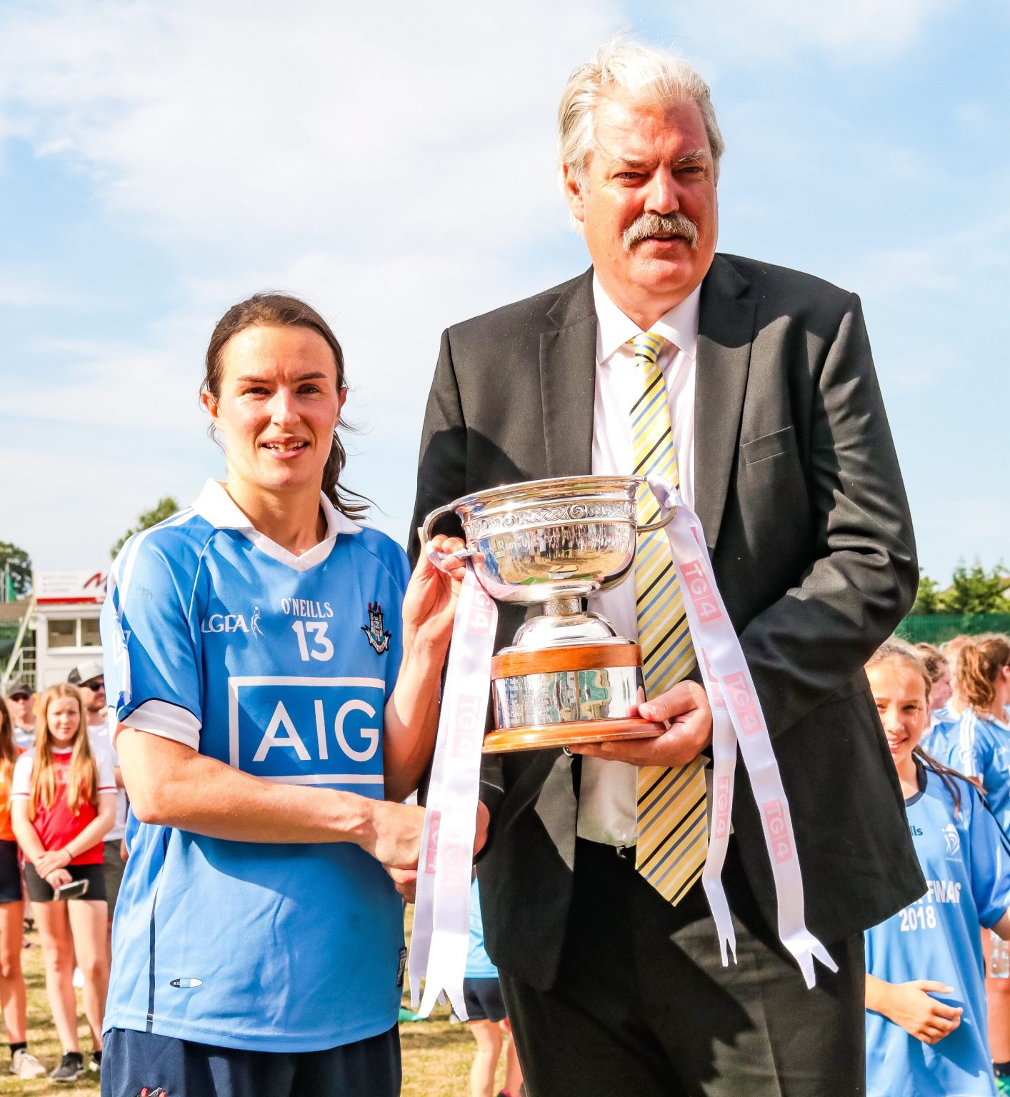 Dublin Ladies Football Captain Sinead Aherne Is Presented With The Leinster Trophy By Leinster LGFA President Dominic Leech in a black suit.