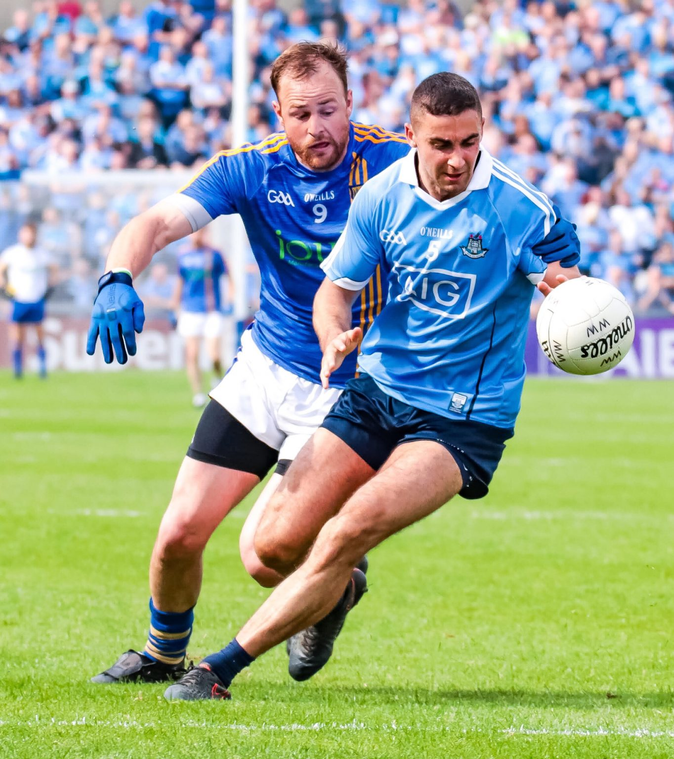 A Dublin player in a sky blue jersey and navy shorts battling for the ball with a Wicklow player in a blue jersey with yellow stripes as Dublin maintained the unbeaten away record