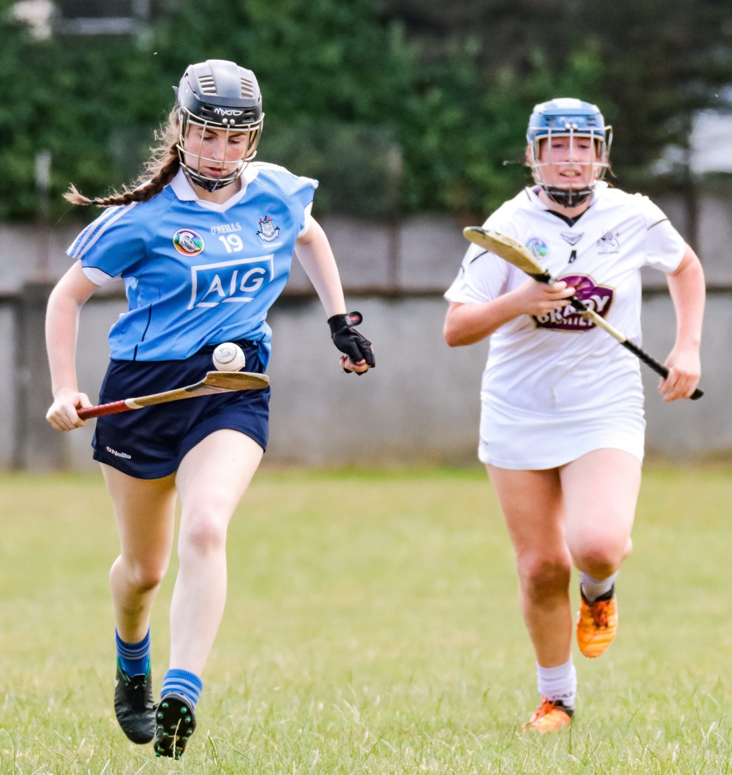 Dublin Minor Camogie Player in sky blue jersey races away with the ball balancing on her hurl from a Kildare player in a white jersey during Dublin second half scoring blitz