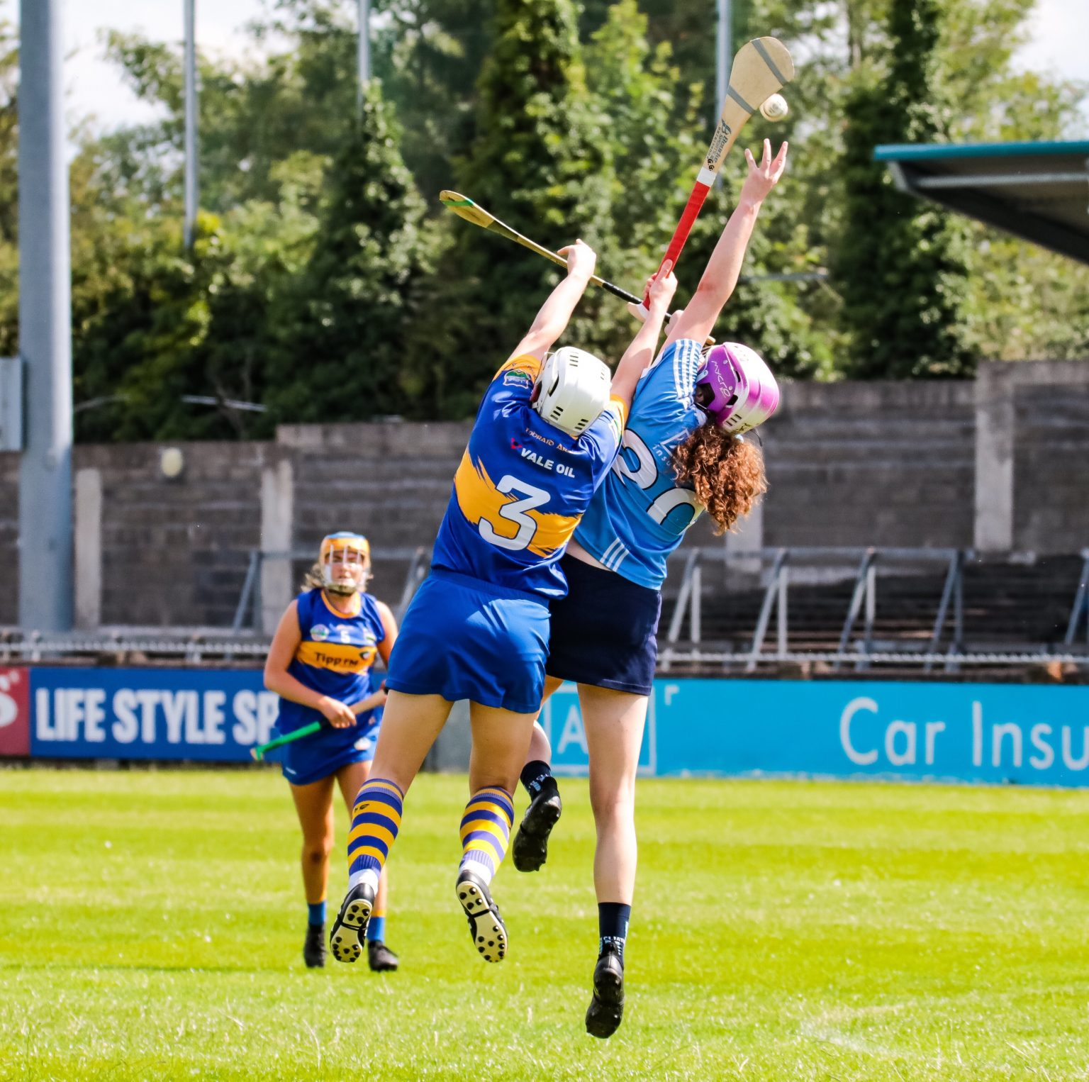 A Dublin Camogie Player wearing a sky blue jersey and pink helmet and a Tipperary player in a blue jersey with yellow band jump for the ball during today's thrilling championship draw