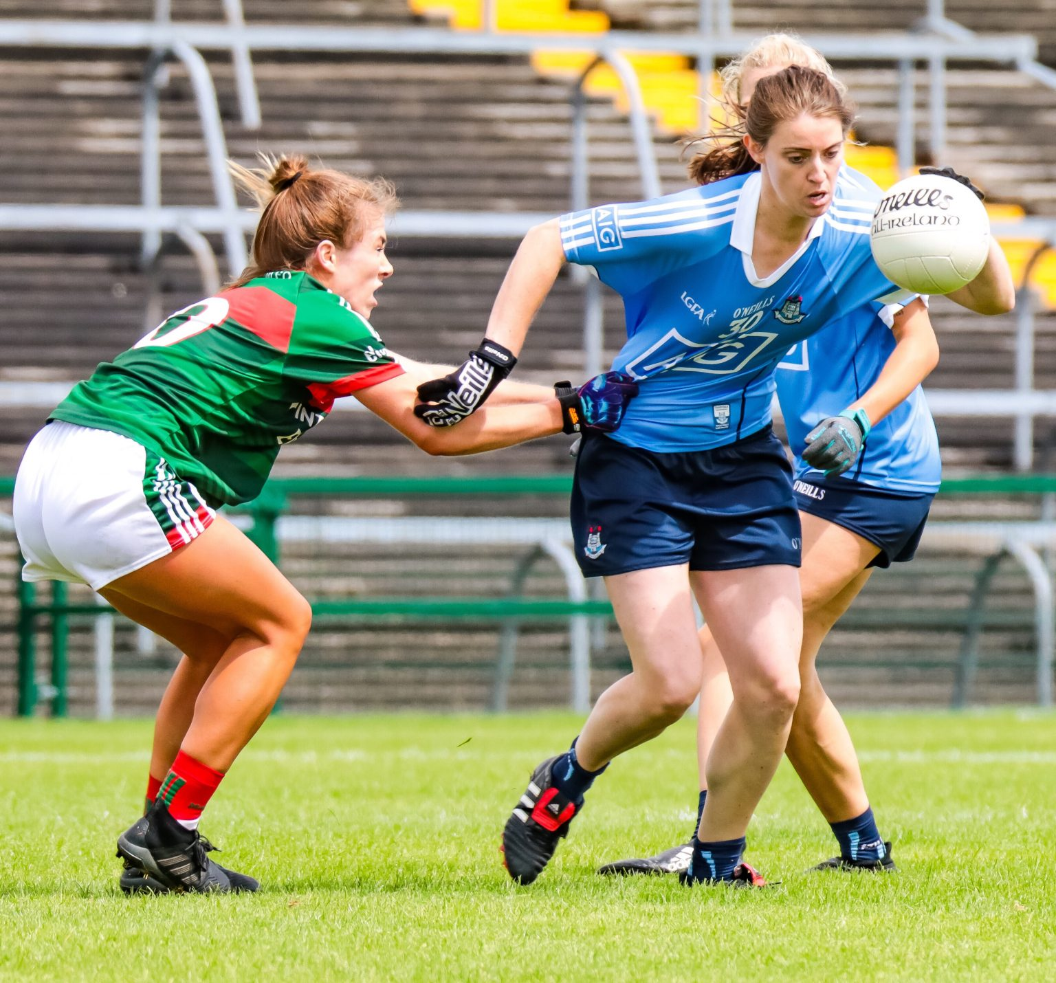 Dublin Ladies Footballer in a sky blue jersey and navy shorts breaks away from a Mayo player in a green and red jersey