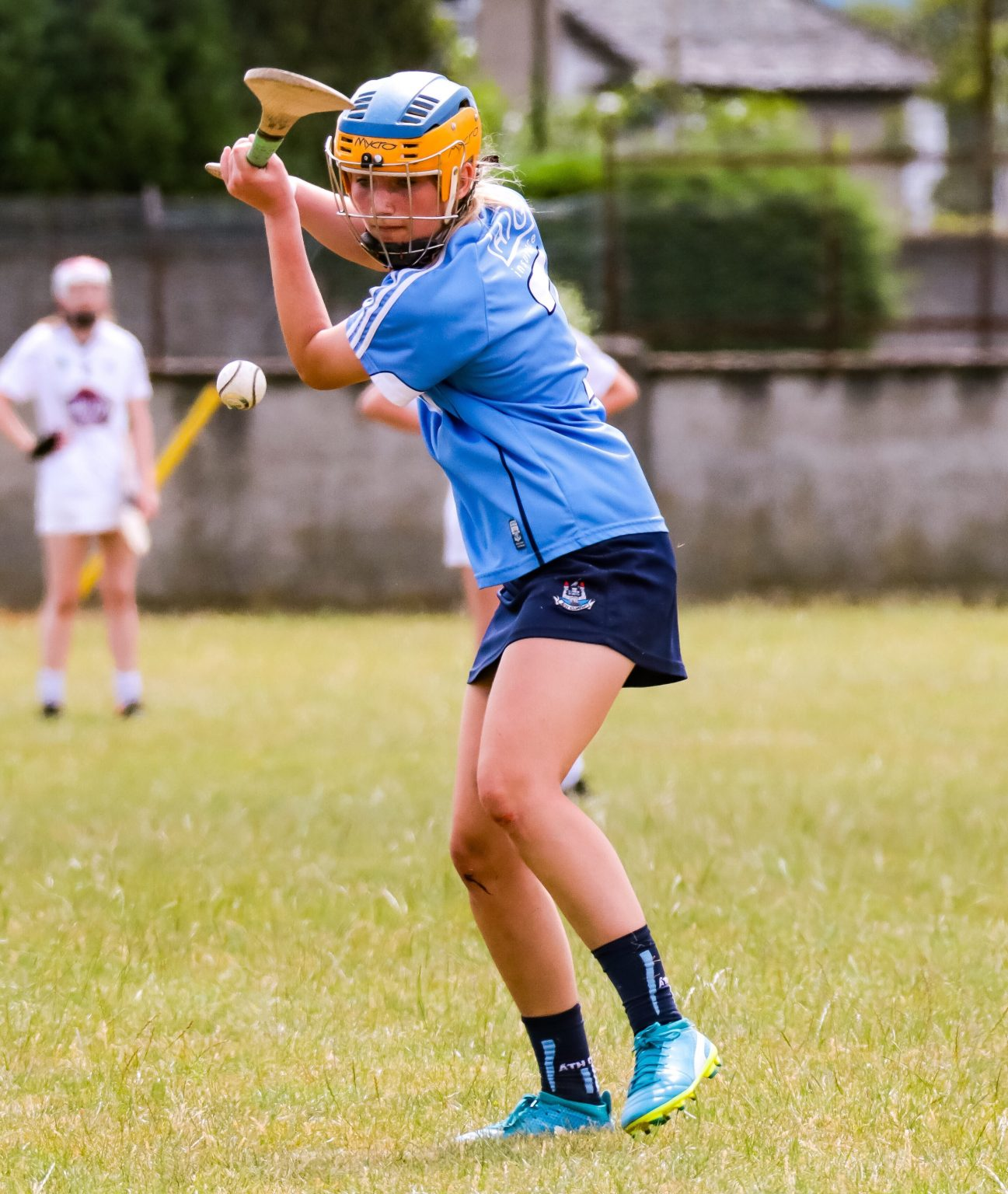 Dublin Minor Camogie Player in a sky blue jersey, navy skort and blue and yellow helmet about to strike the ball the Dublin Minors will be aiming to Claim two Leinster titles