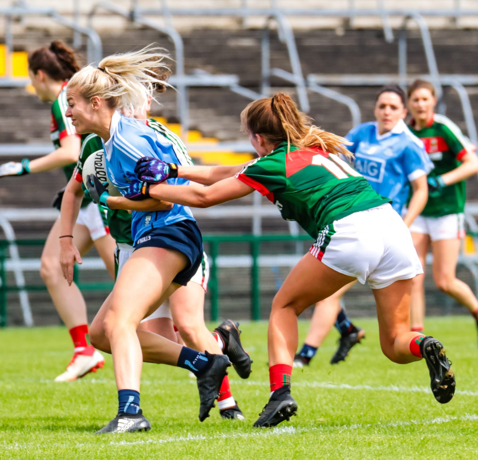 A dublin Ladies footballer in a sky blue jersey gets close attention from a Mayo player in a green and red jersey during Dublin's win which seen them advance to the All Ireland quarter finals
