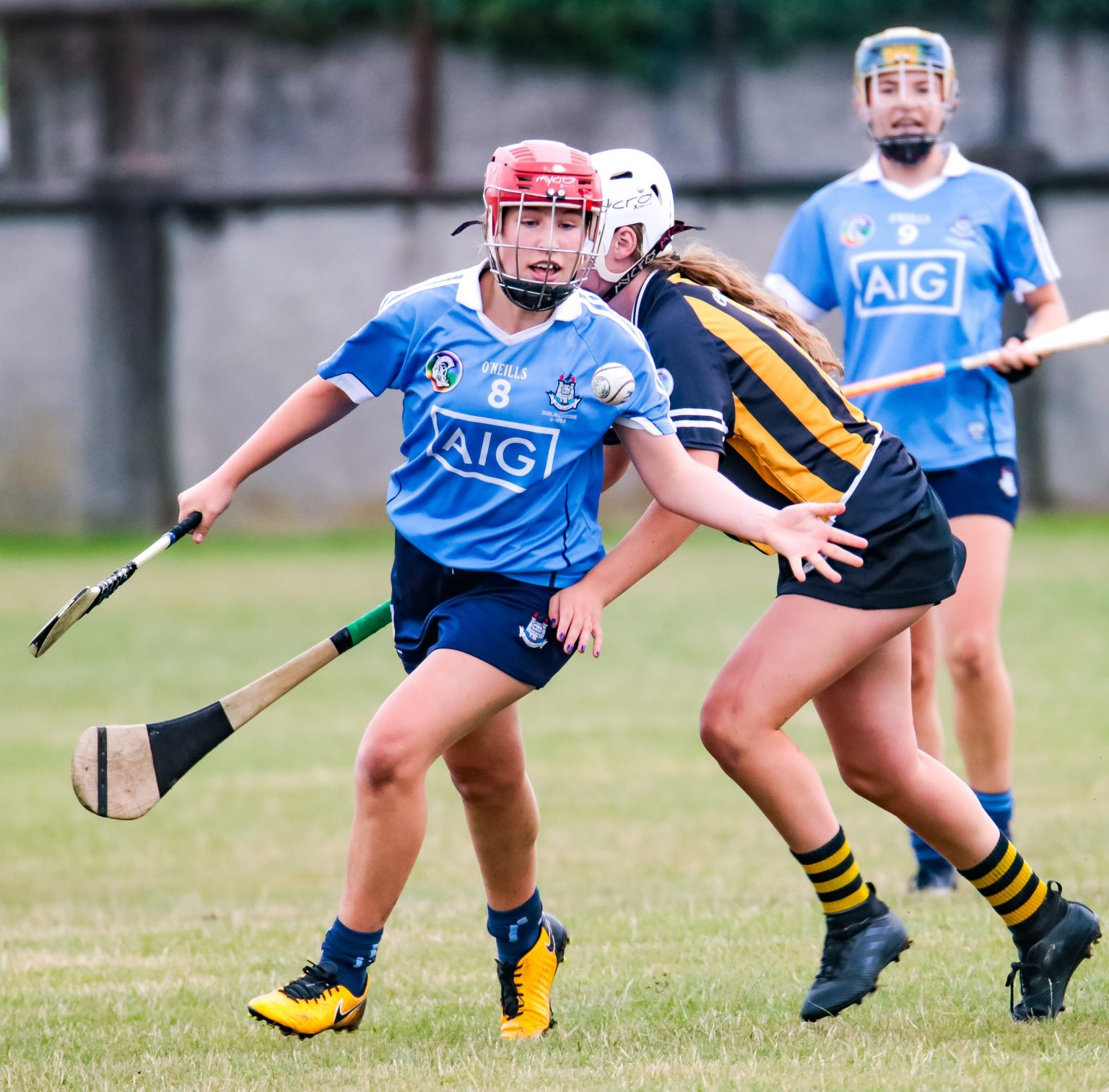 Dublin Camogie Player in a sky blue jersey, navy skort and red helmet hand passing the ball Dublin face Galway in the championship quarter final