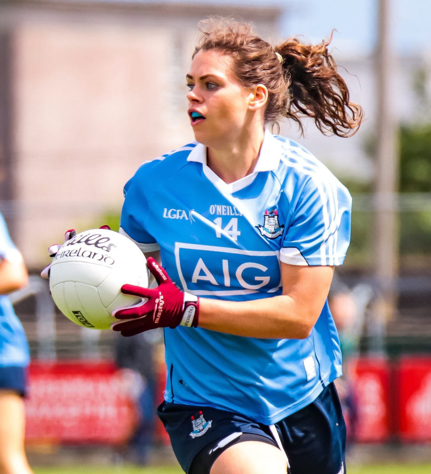 A dublin Ladies footballer in a sky blue jersey looks ahead to see where to pass the ball