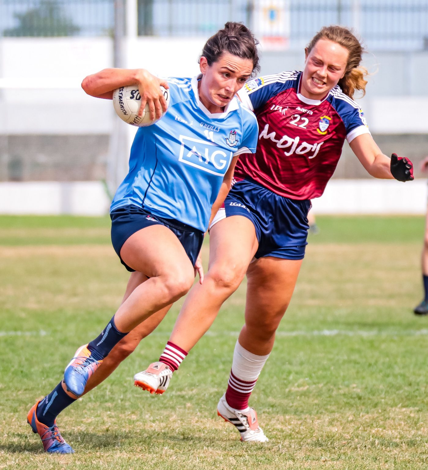 Dublin player in sky blue jersey with a white ball in her right hand charges past a Westmeath player in a Maroon Jersey