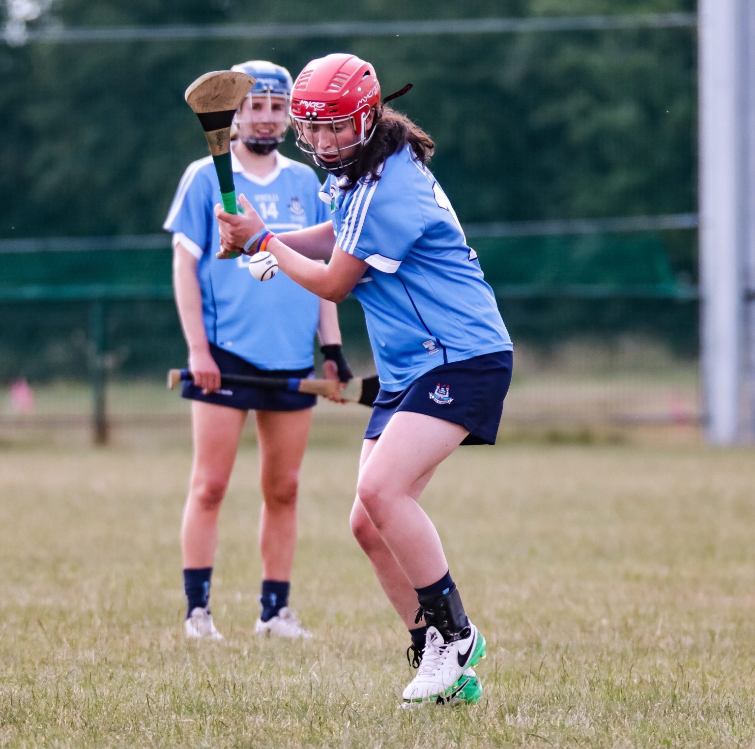 Dublin Camogie Player in a sky blue jersey, navy skort and red helmet about to strike the ball with her hurl during a Camogie championship game