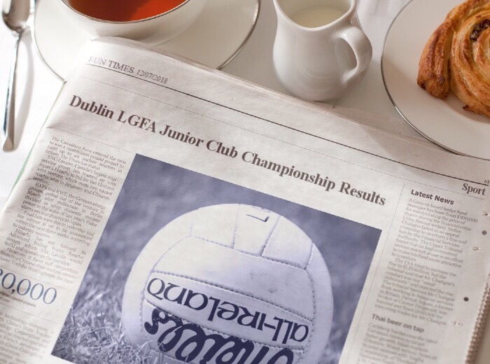 A newspaper on a table with the headline Dublin LGFA Junior Championship Results and a picture of a white ball