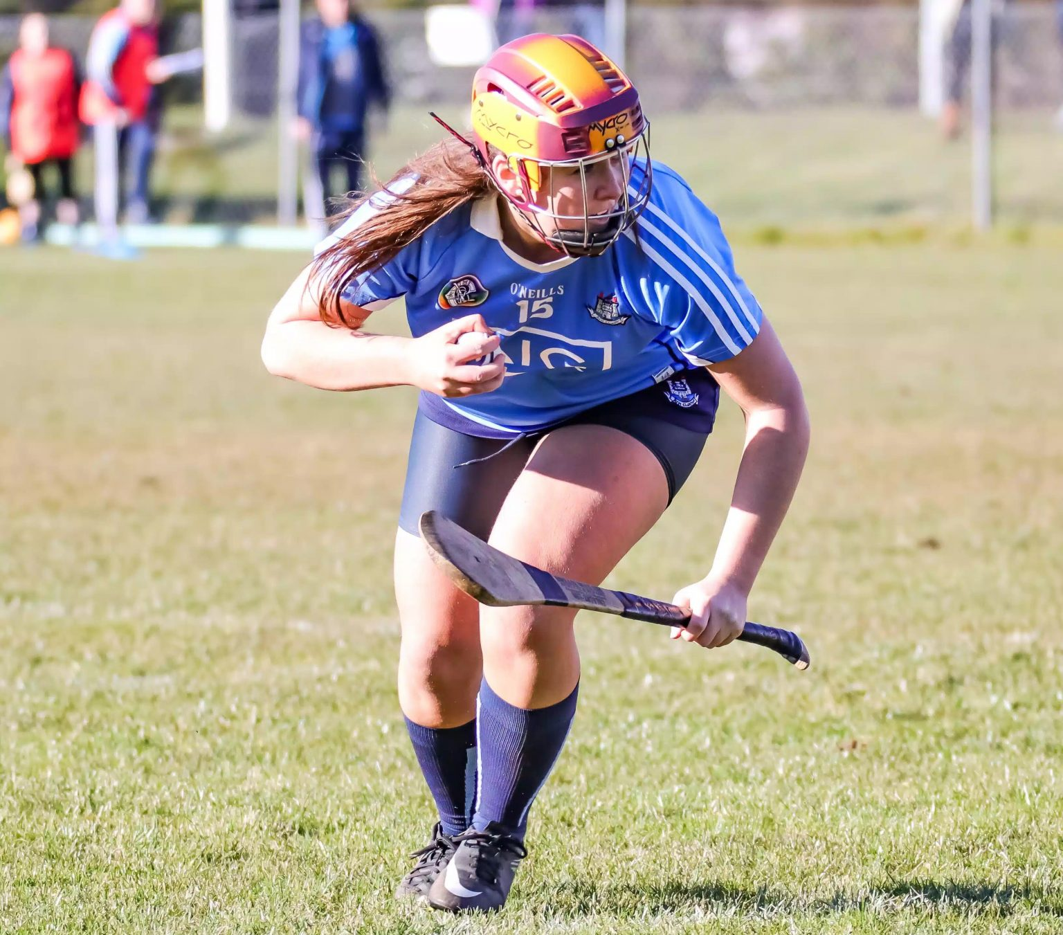 Dublin Premier Junior Camogie Player in a sky blue jersey, navy skort, red and yellow helmet with the ball in her right hand and hurl in left hand during Dublin's win to qualify for the All Ireland semi final