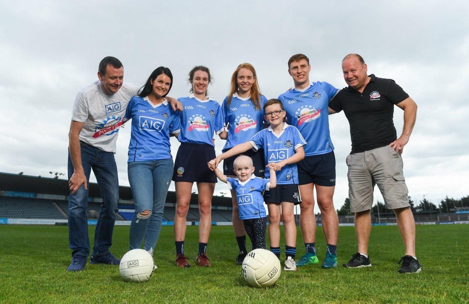 A Dublin Men's and Ladies football player and camogie player pose for a photo in Parnell Park with members of Aoibheann's Pink Tie Charity for the announcement that Dublin sponsors AIG will be giving up the advertisement space on the Dublin jersey for the charity for the teams upcoming games
