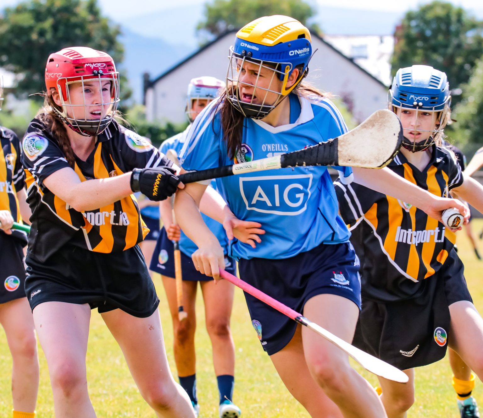 Dublin Camogie Player in sky blue jersey, navy skort and yellow and blue helmet breaking the tackle of a Kilkenny player in an amber and black striped jersey, black skort and red helmet as Four first half goals secured victory for Dublin
