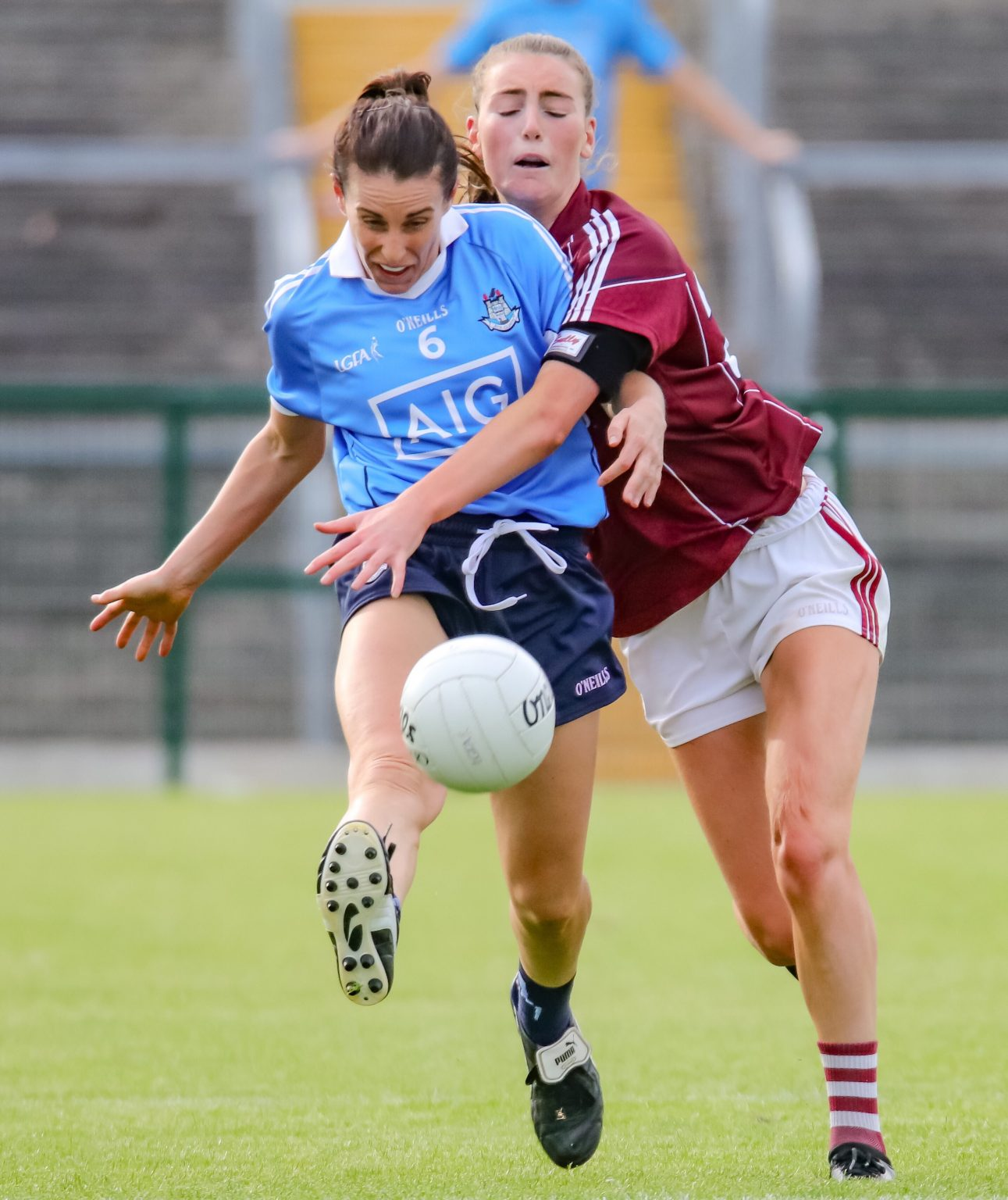 A dublin Ladies footballer in a sky blue jersey and navy shorts gets her kick away despite the attentions of a Galway player in a maroon jersey and white shorts