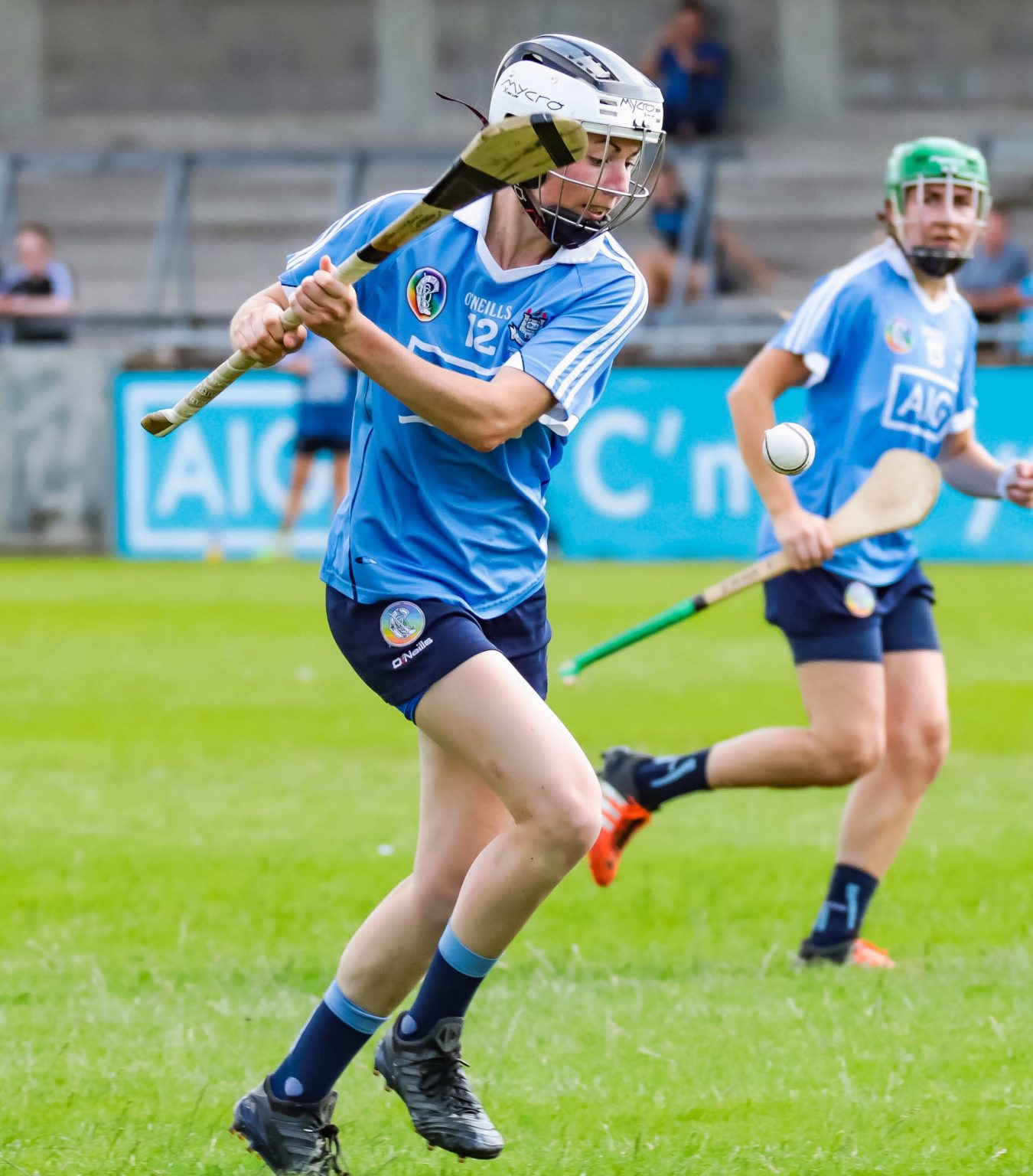Dublin Camogie player in a sky blue jersey, navy skort and black and white helmet striking the ball with her hurl as Dublin who are underdogs face Galway in the quarter finals