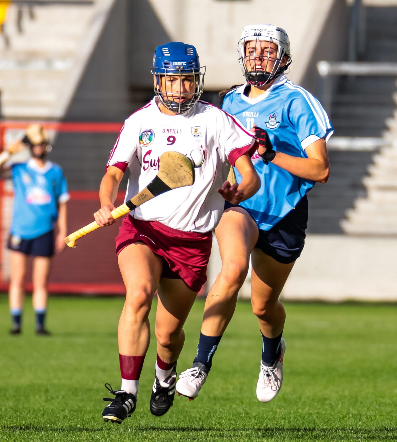 A Galway camogie player in a white jersey, maroon skort and dark blue helmet breaks away with the ball on her hurl from a dublin player in sky blue jersey, navy skort and white helmet