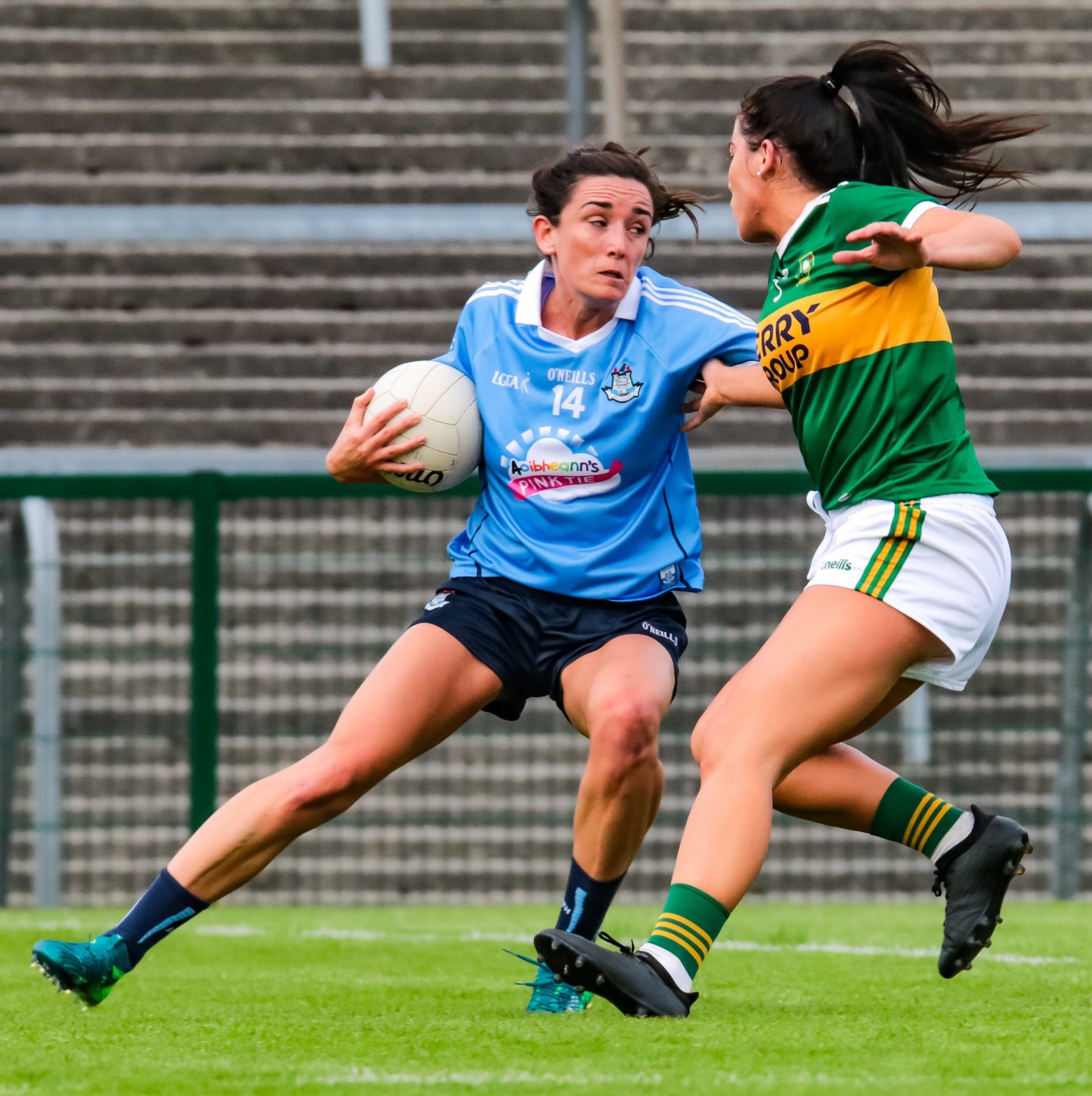 A Dublin Ladies footballer in a sky blue jersey and navy shorts evades a tackle from a Kerry player in a green jersey and white shorts